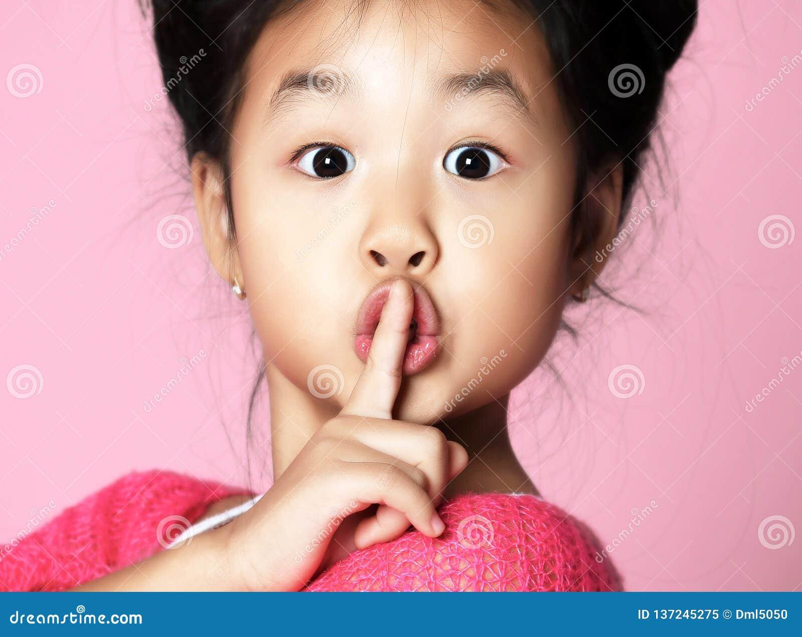 La ragazza asiatica del bambino in maglione rosa mostra shhh il segno calmo sul rosa