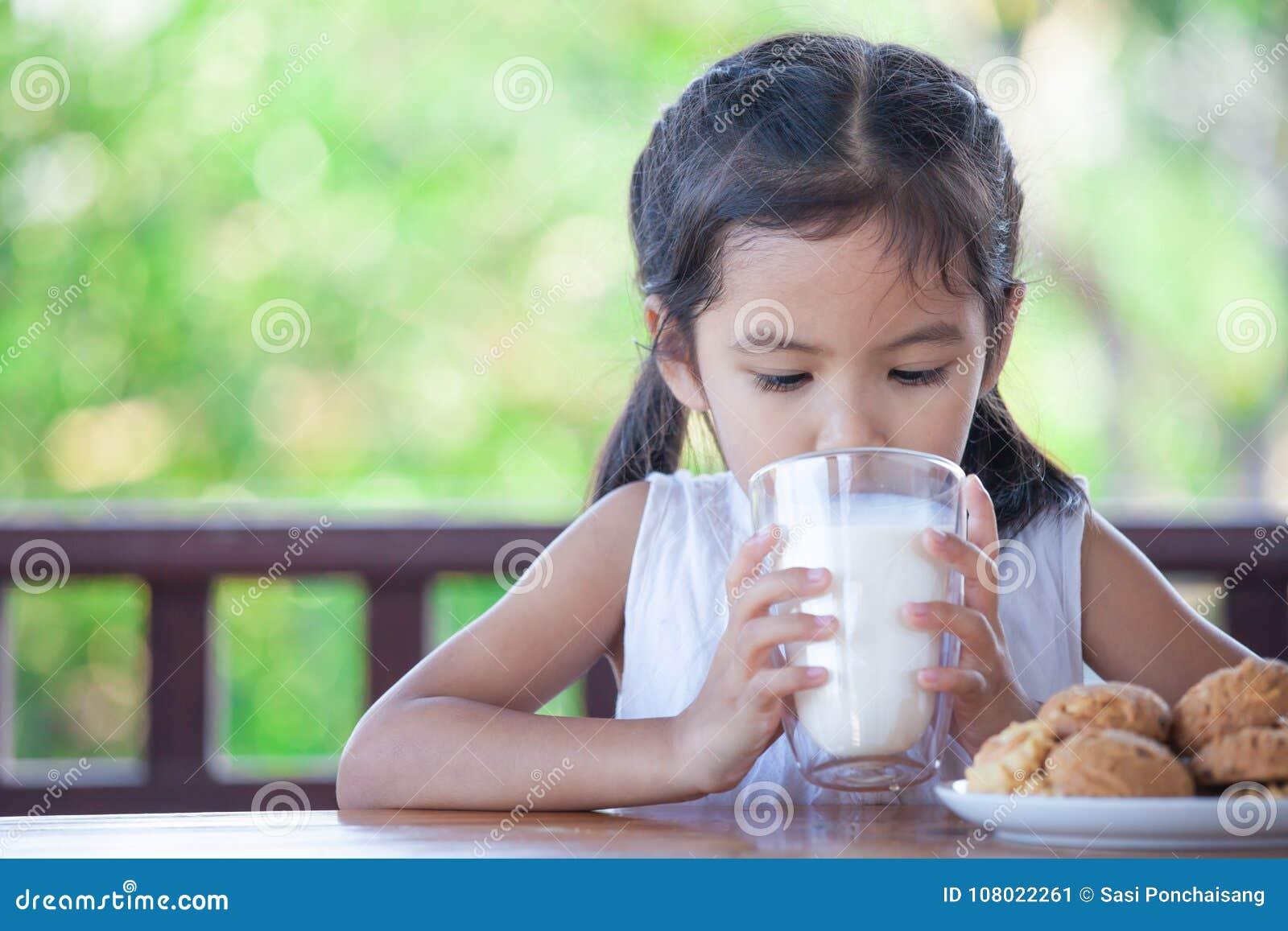 La ragazza asiatica sveglia del piccolo bambino sta bevendo un latte da vetro
