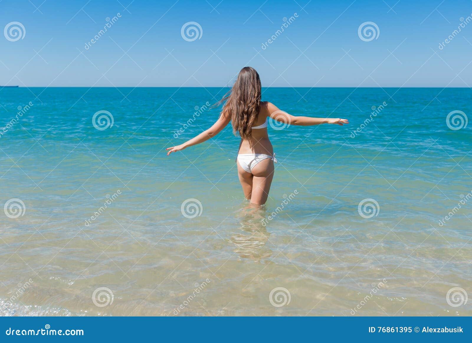 00969bf823d7 La Ragazza In Bikini Bianco Entra Nel Mare Immagine Stock - Immagine ...