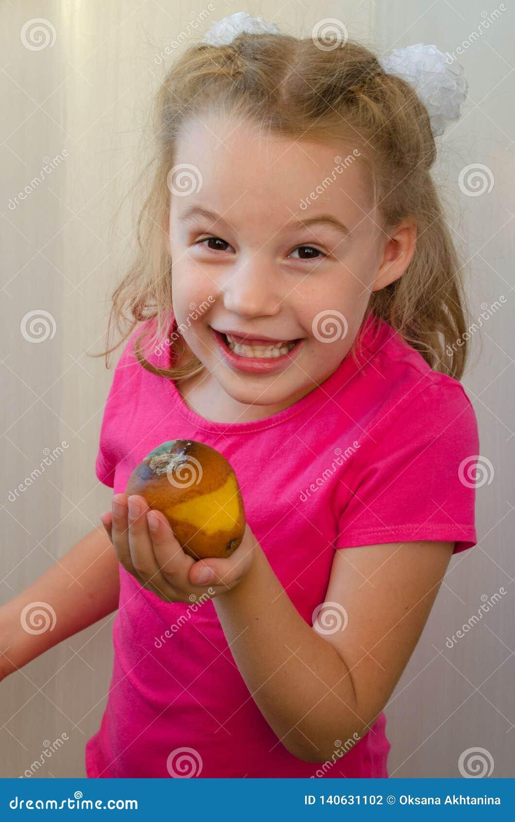 La ragazza bionda con un sorriso offre una pera marcia