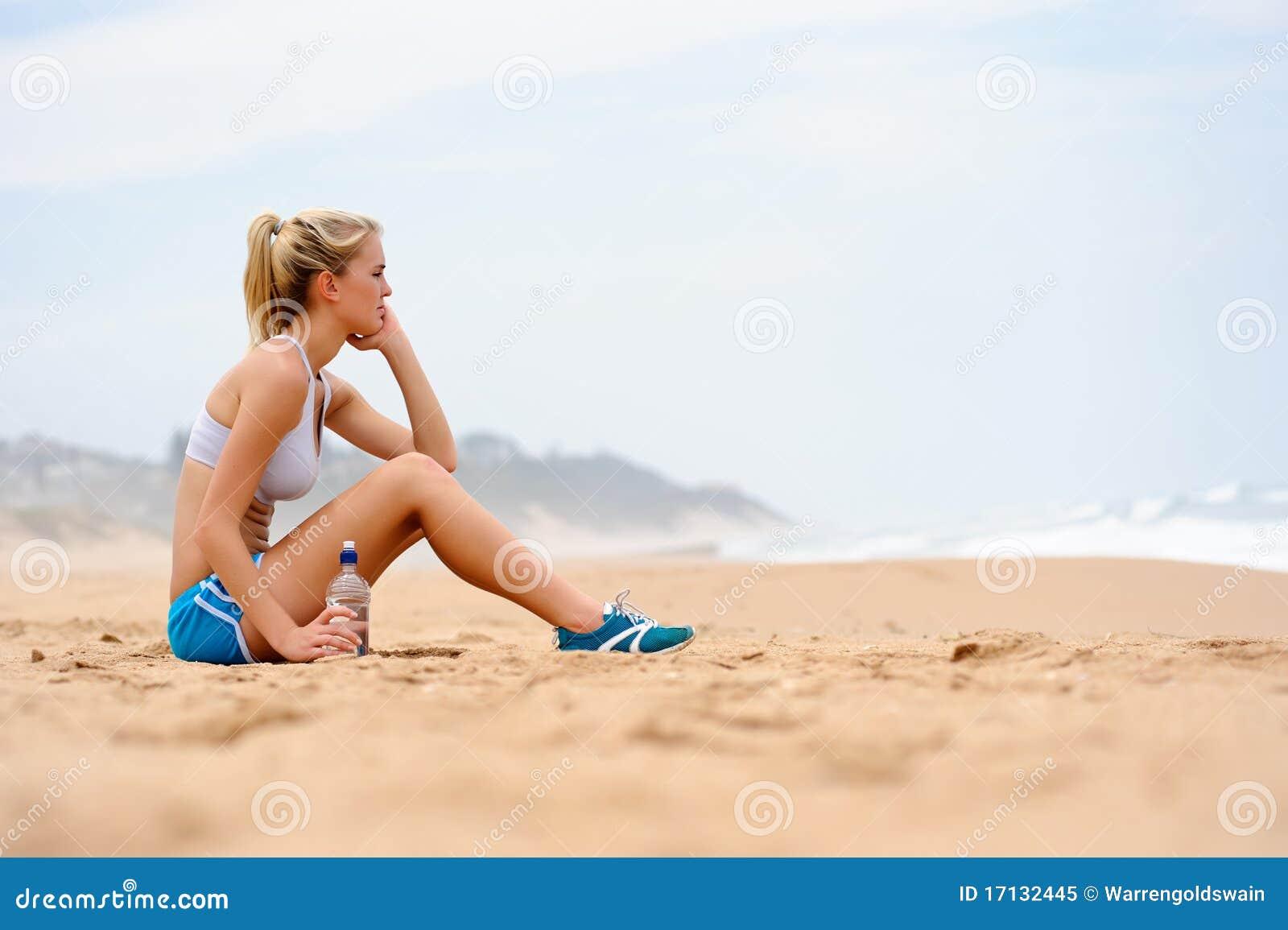 Stock Libera Da Diritti La Ragazza Bionda Si Siede Sulla Spiaggia