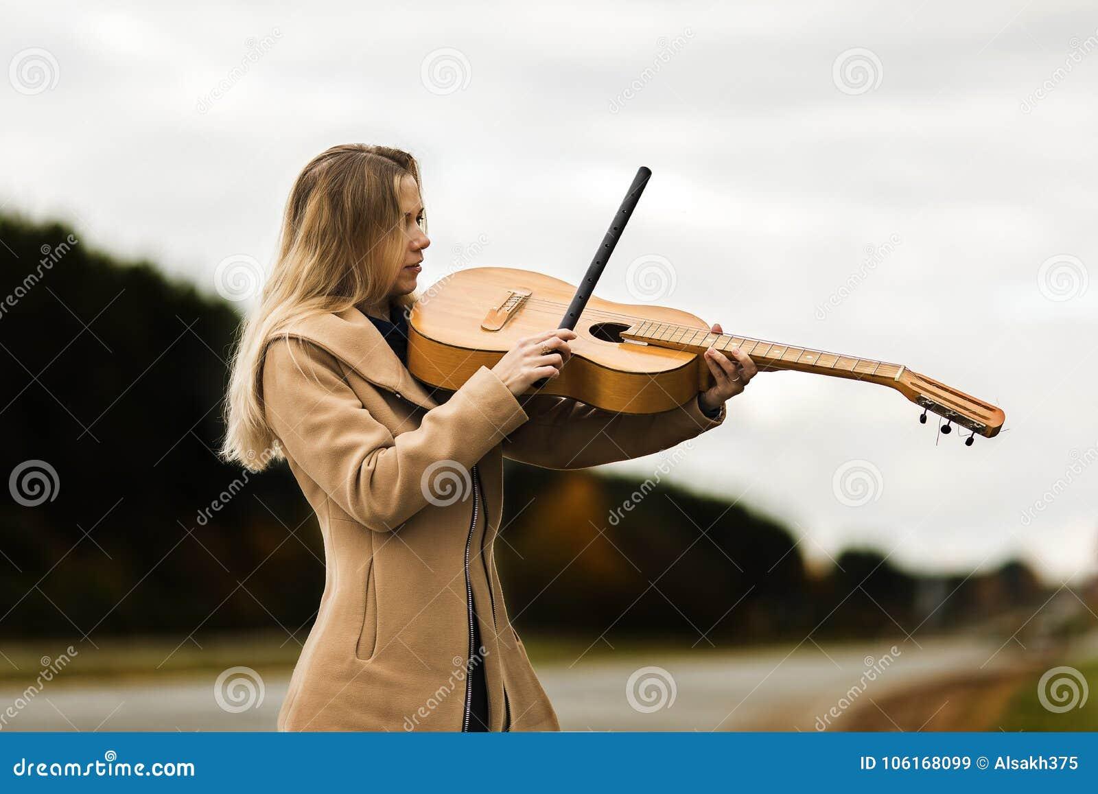La ragazza bionda in un cappotto beige gioca la chitarra come un violino che sta sull orlo dell autostrada di autunno