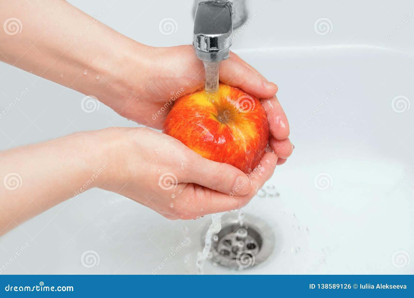 La ragazza caucasica lava una mela sotto l acqua corrente
