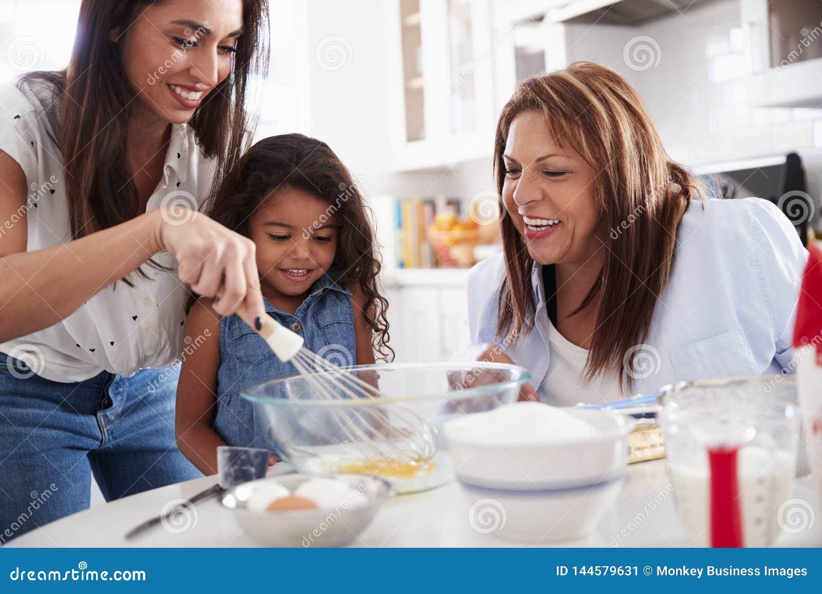 La ragazza che fa un dolce nella cucina con la sue mummia e nonna, si chiude su
