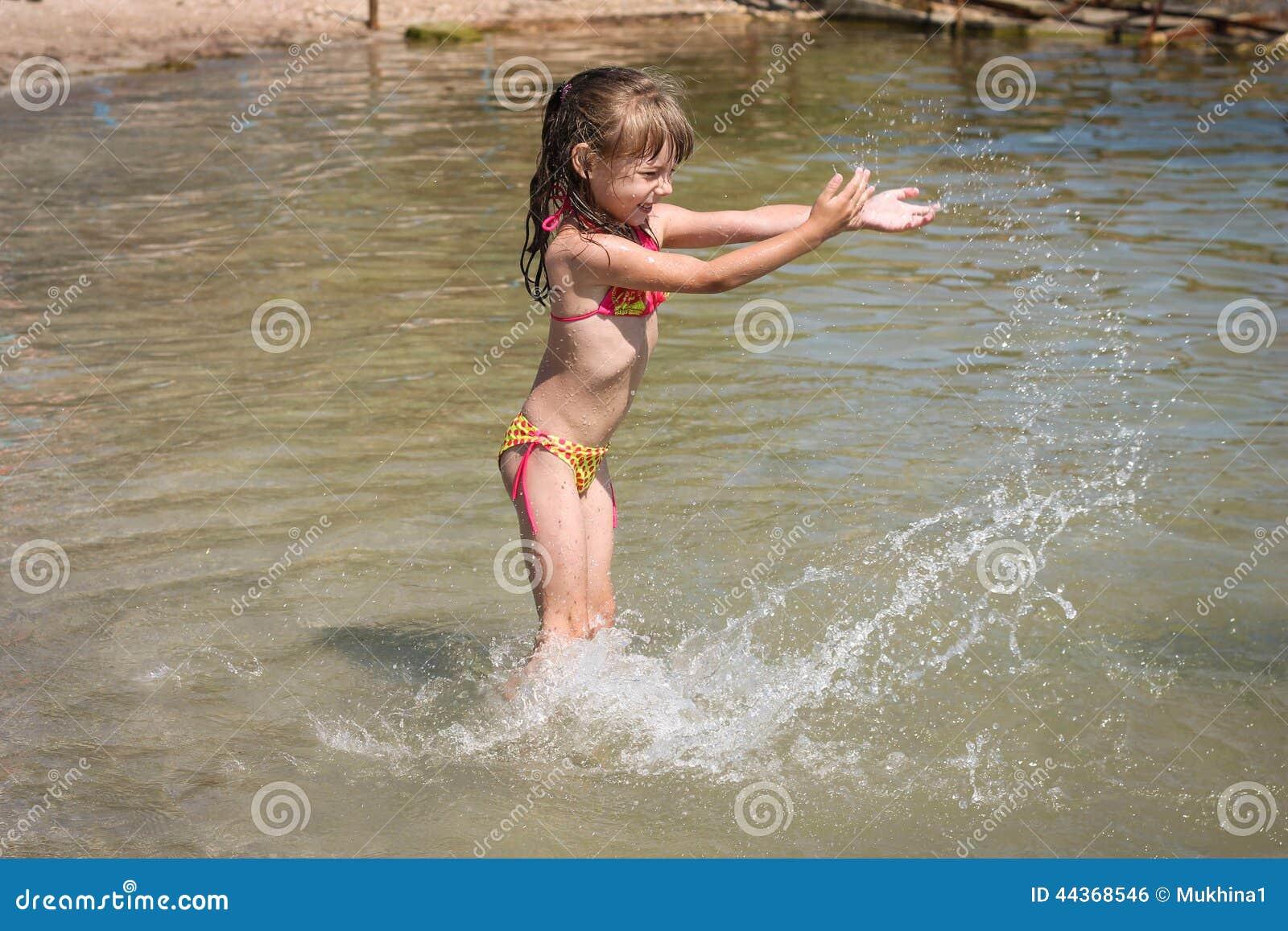 La ragazza che gioca sul mare, spruzza l acqua