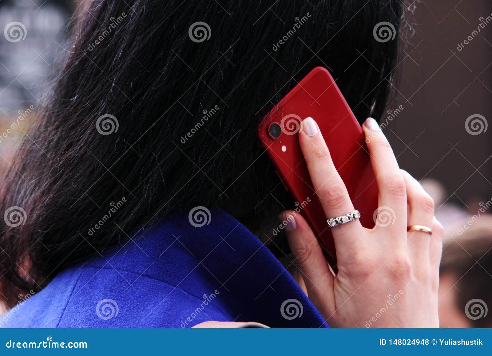 La ragazza chiama su un telefono cellulare Isolato su bianco