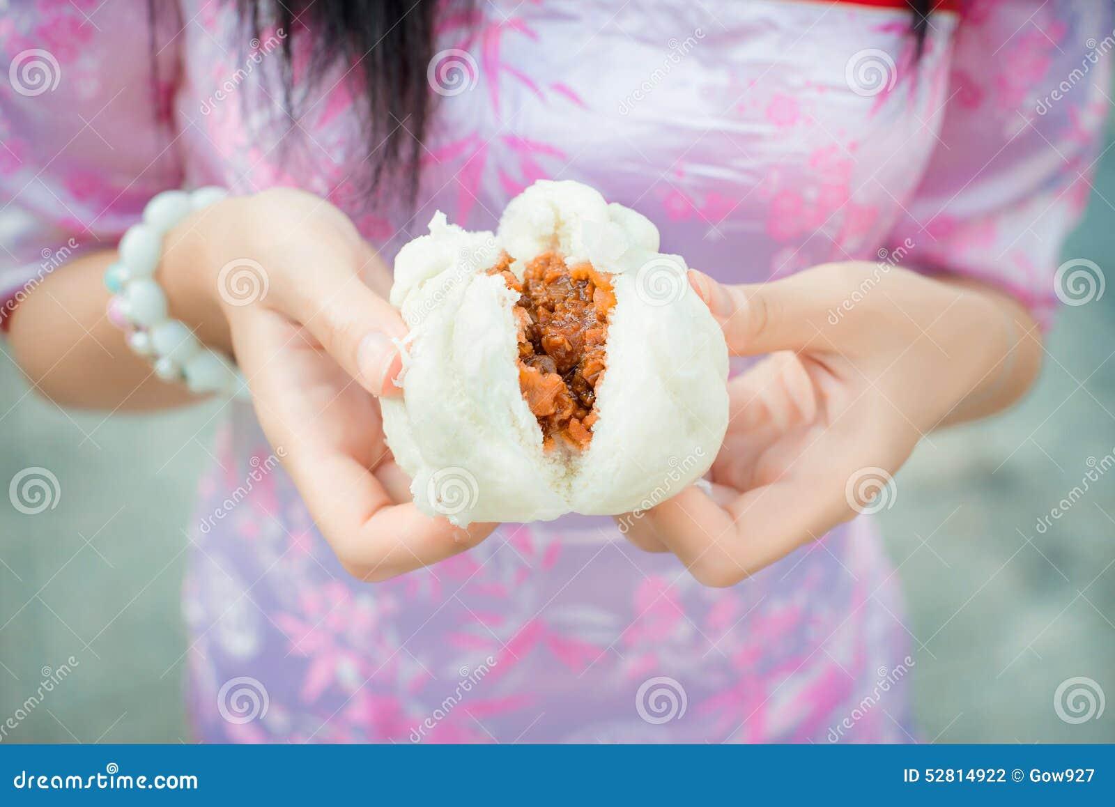 La ragazza cinese nel cheongsam sta strappando il panino cotto a vapore della roba steamed