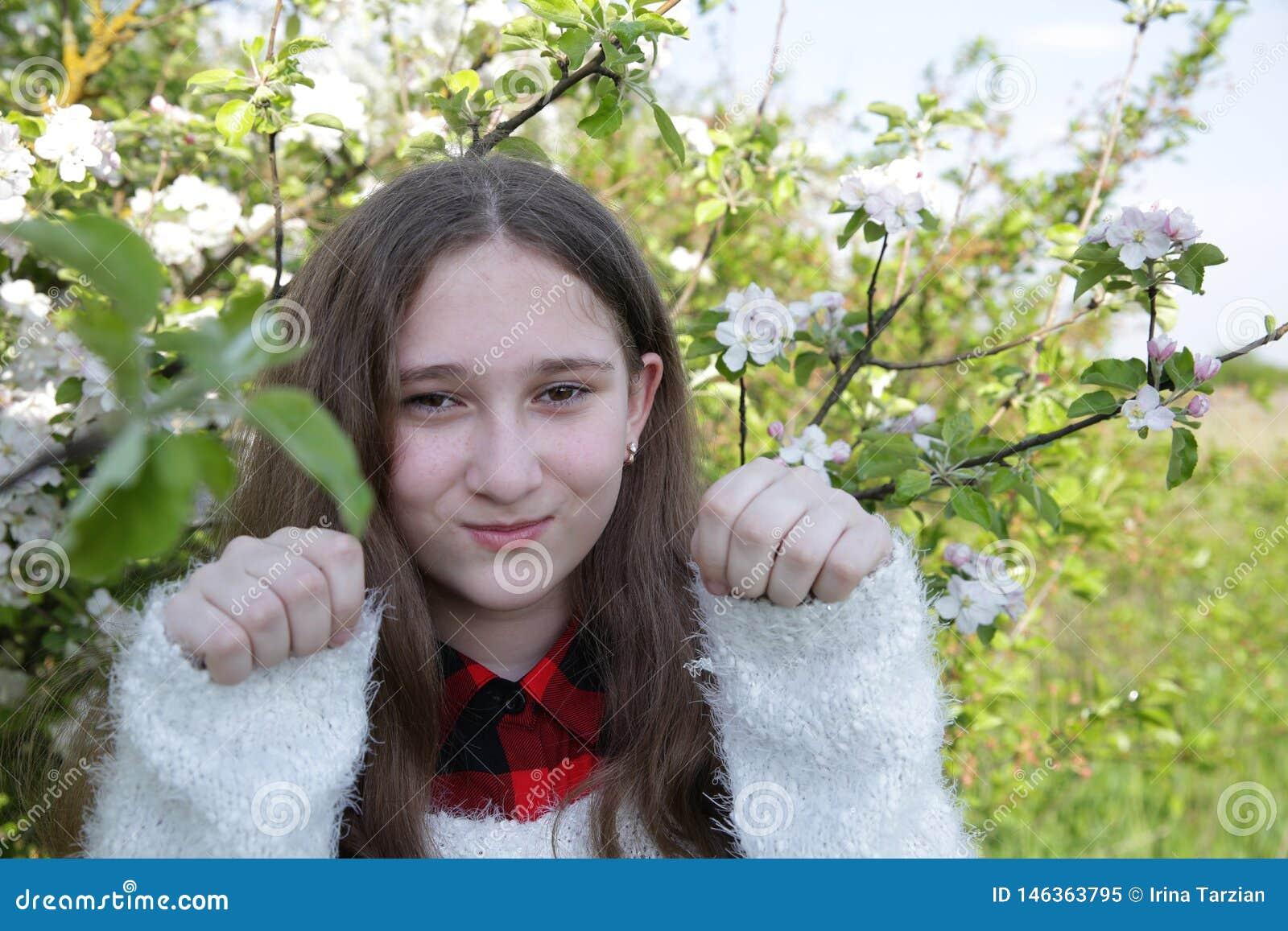 La ragazza con capelli lunghi tiene i pugni su sui precedenti degli alberi di fioritura su un fondo vago molle