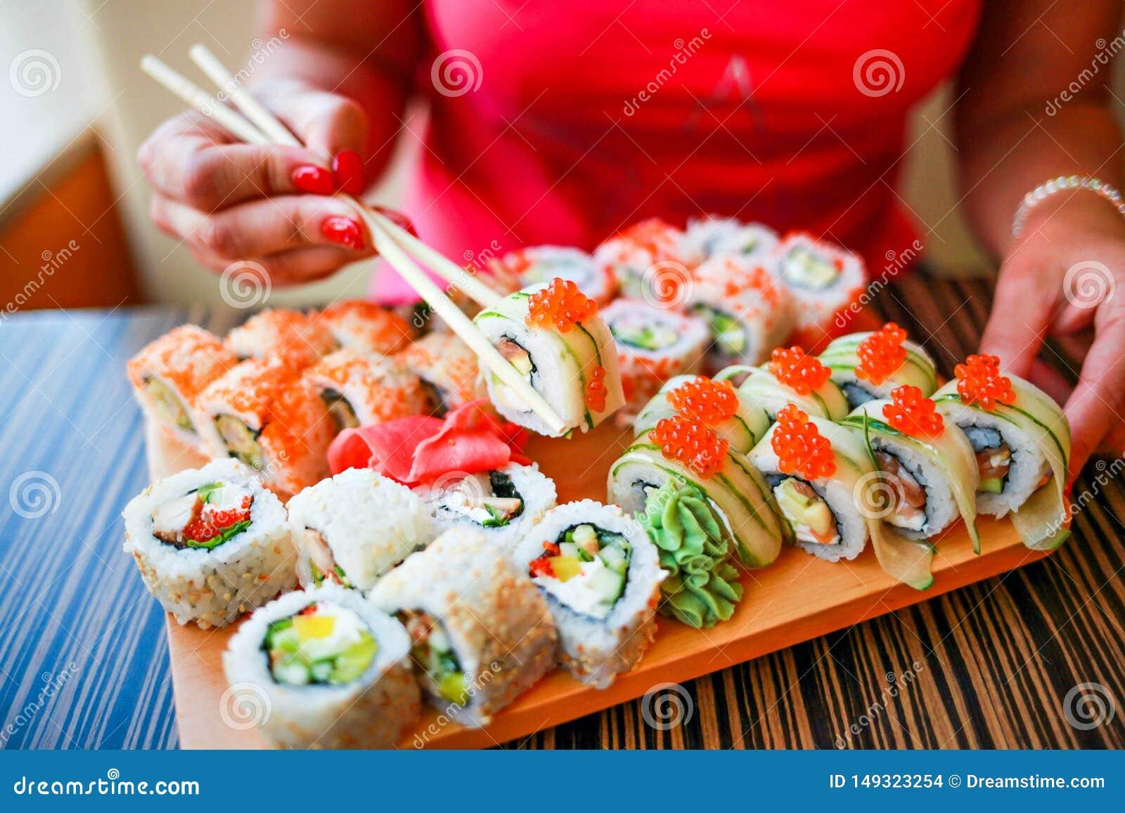 La ragazza con le mani ben curato tiene i bastoncini per i sushi La ragazza mangia un grande insieme dei sushi