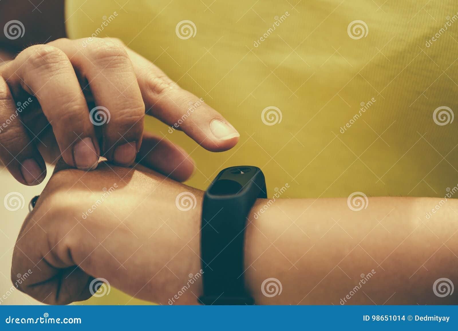 La ragazza controlla l impulso sul pedometro del braccialetto di forma fisica o dell inseguitore di attività sul polso, sullo spo