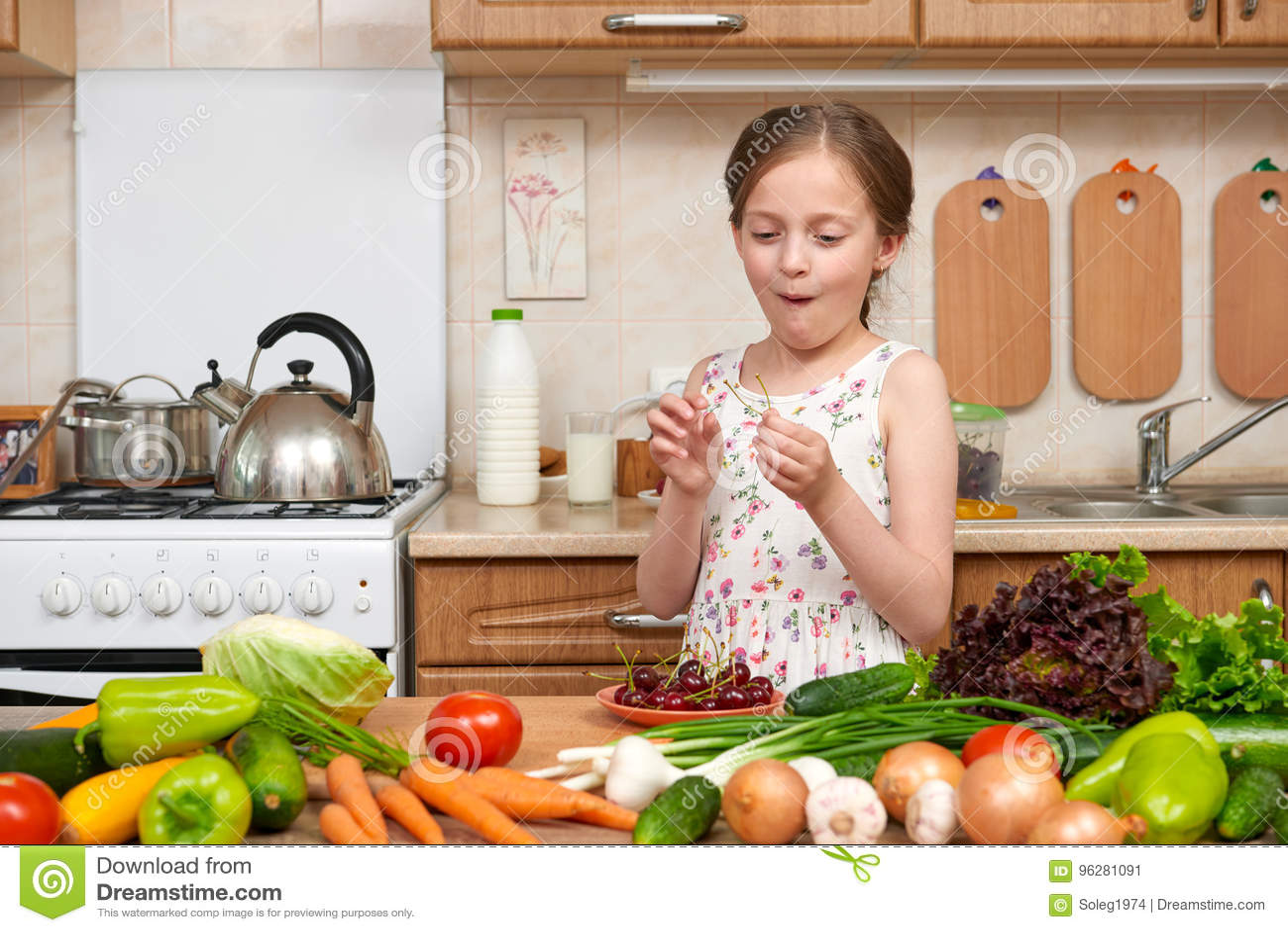 La ragazza del bambino mangia le ciliege, la frutta e le verdure in cucina domestica interna, concetto sano dell alimento