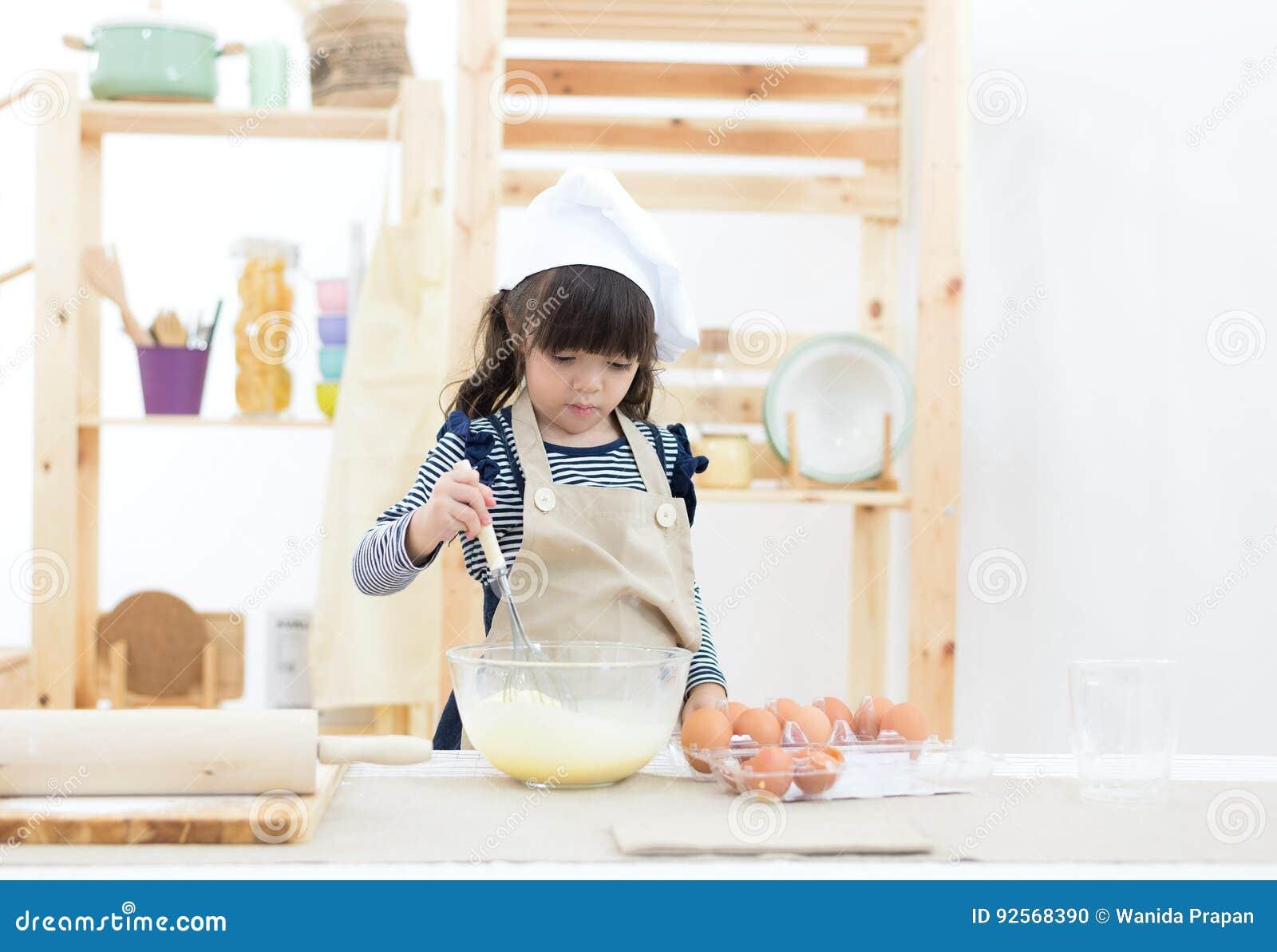 La ragazza del bello bambino sta cucinando i biscotti