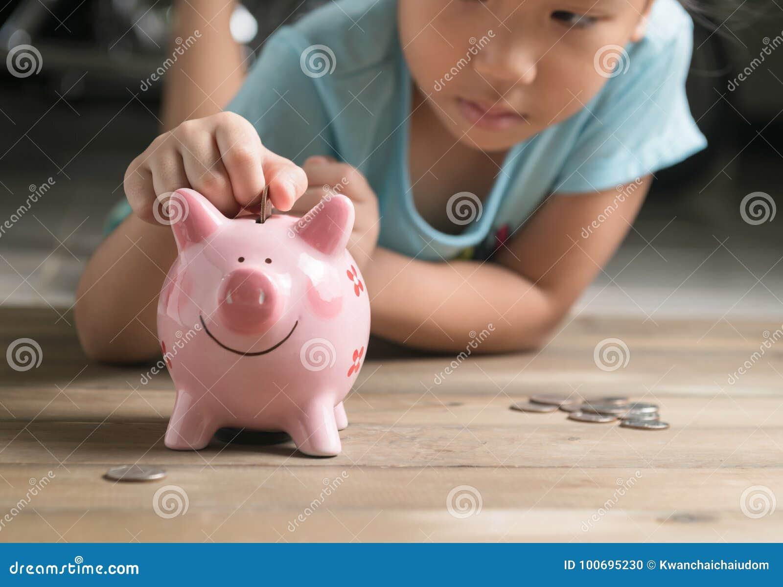 La ragazza della mano ha messo la moneta al porcellino salvadanaio, risparmiante i soldi
