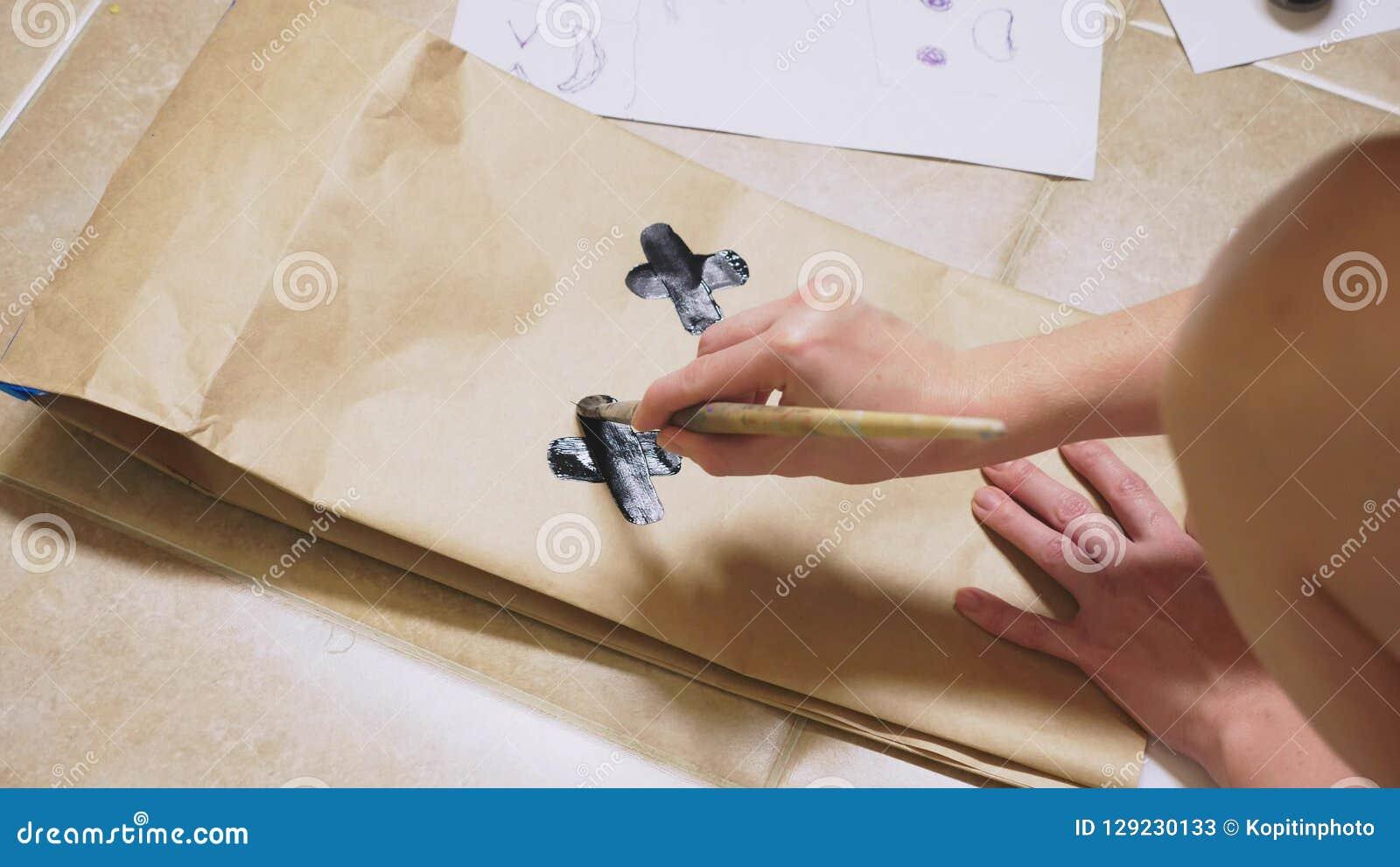 La ragazza disegna con una spazzola sulle varie emozioni dei sacchi di carta Il concetto delle emozioni negli smiley