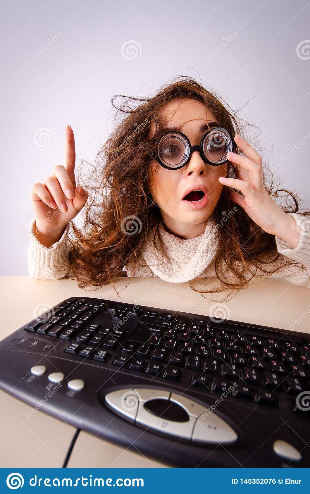 La ragazza divertente del nerd che lavora al computer