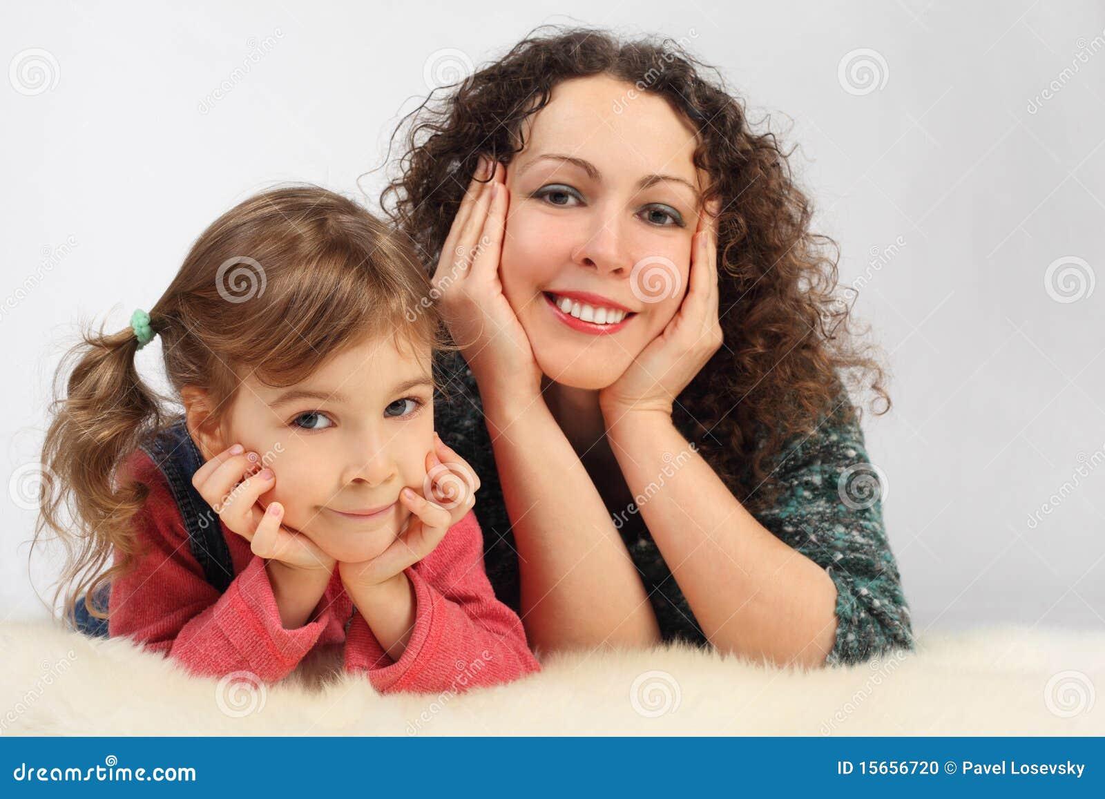 La ragazza e la sua madre con le bugie toothy di sorriso sopra sono caduto