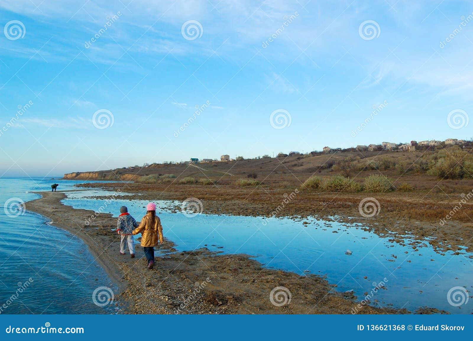 La ragazza e la passeggiata del ragazzo con il padre sulla costa