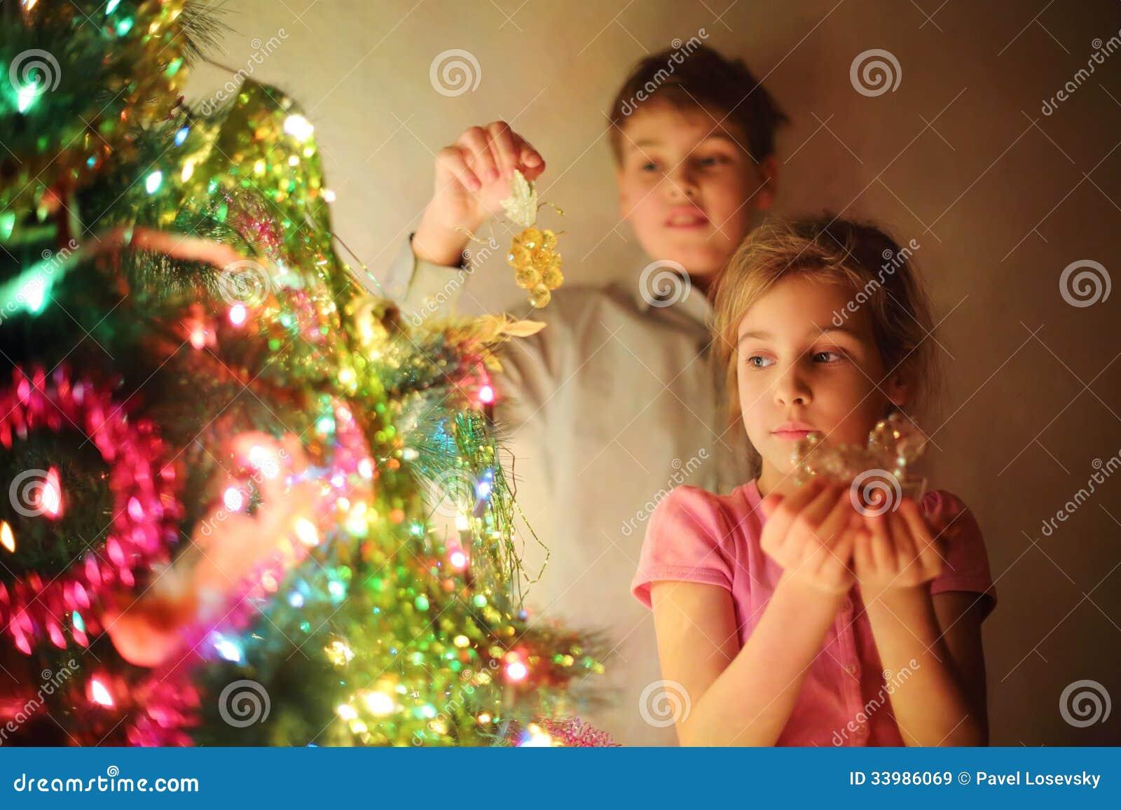 La ragazza ed il ragazzo hanno decorato l albero di Natale dai giocattoli di vetro alla sera.