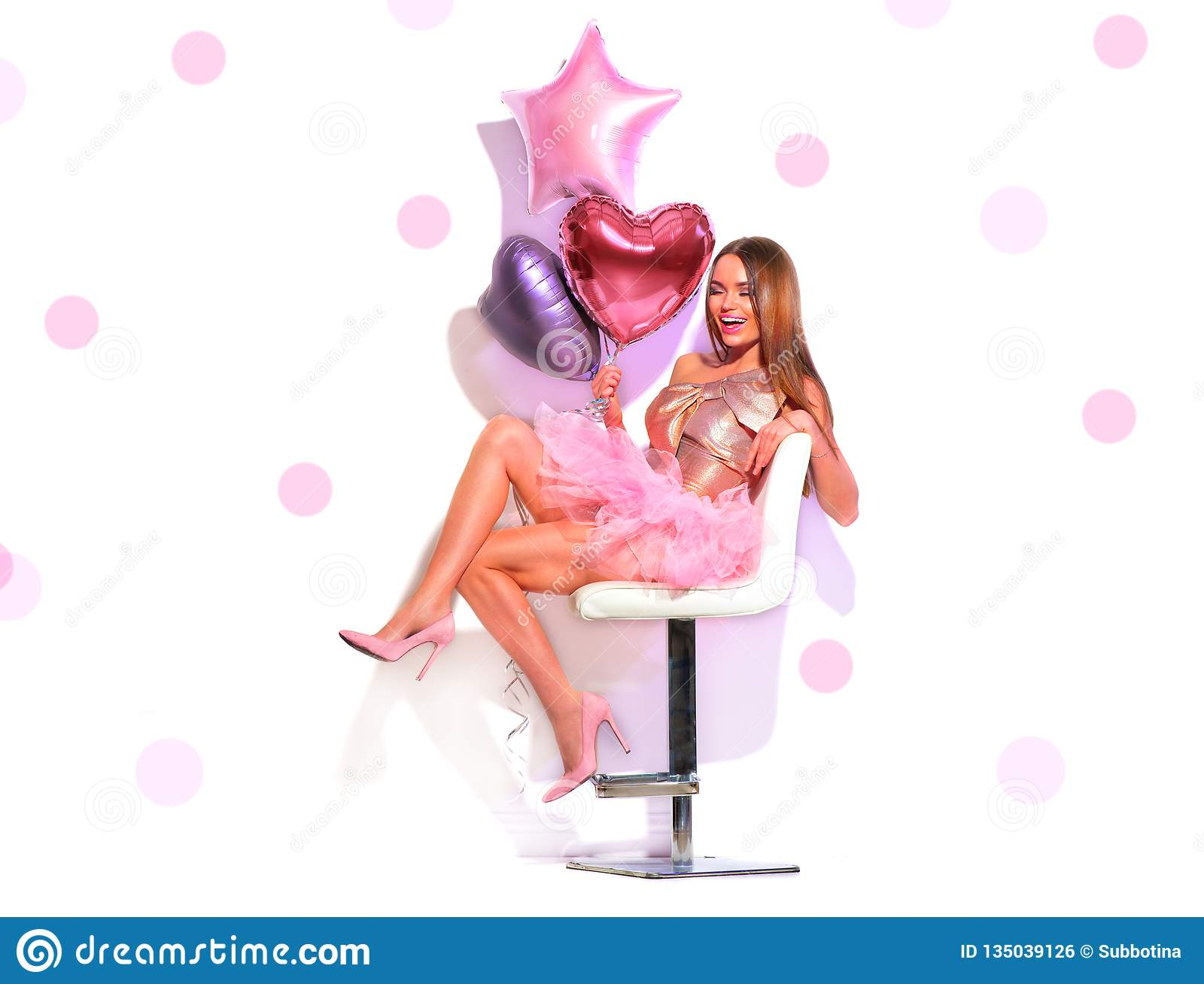 La ragazza facile del modello di moda di bellezza con cuore ha modellato divertiresi degli aerostati, sedentesi sulla sedia Bella