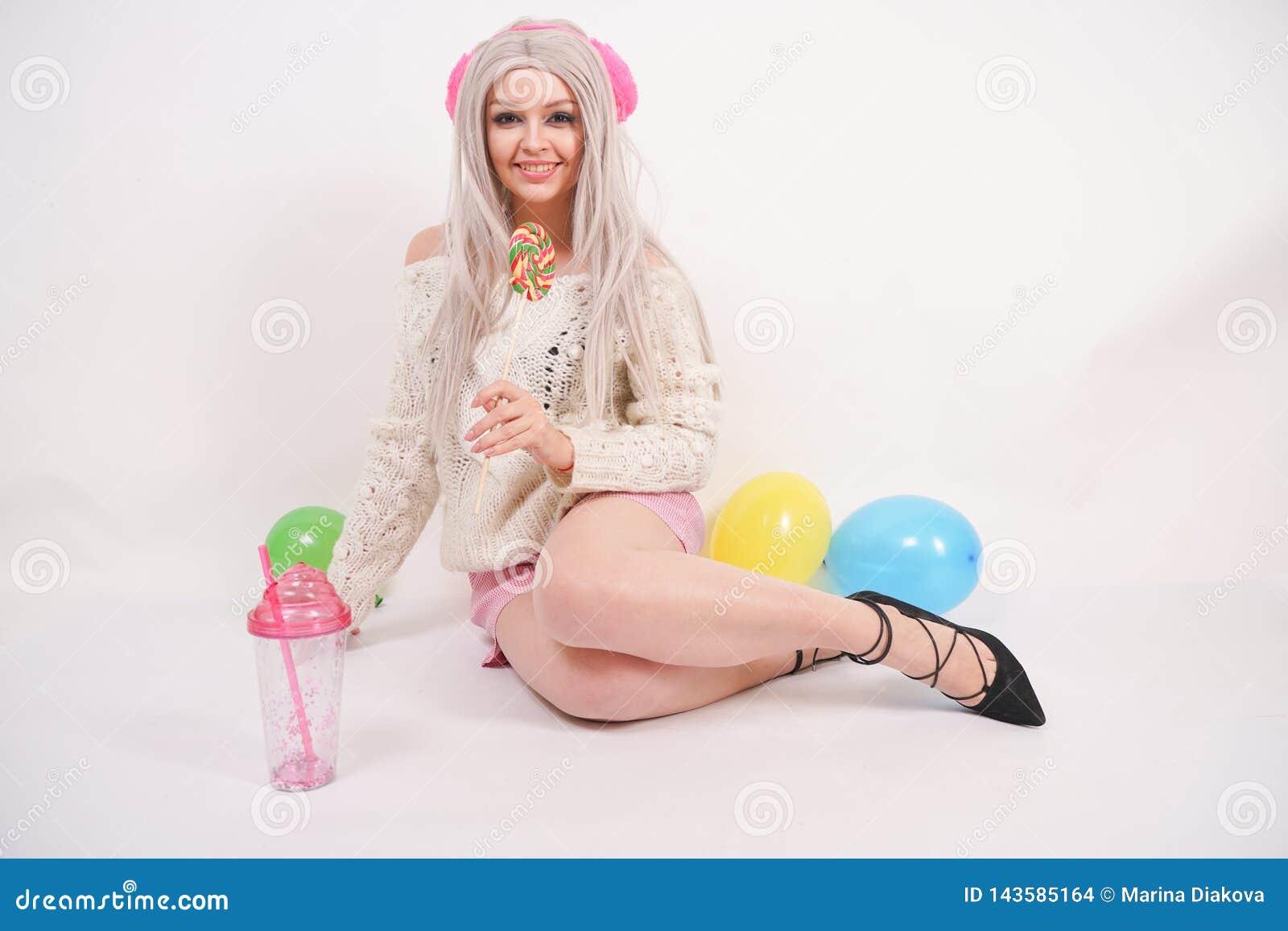 La ragazza felice caucasica bionda sveglia vestita in un maglione tricottato colore latteo e divertente mette, lei si siede sul p