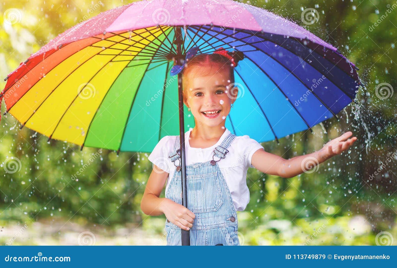 La ragazza felice del bambino ride e gioca sotto la pioggia dell estate con un umbr
