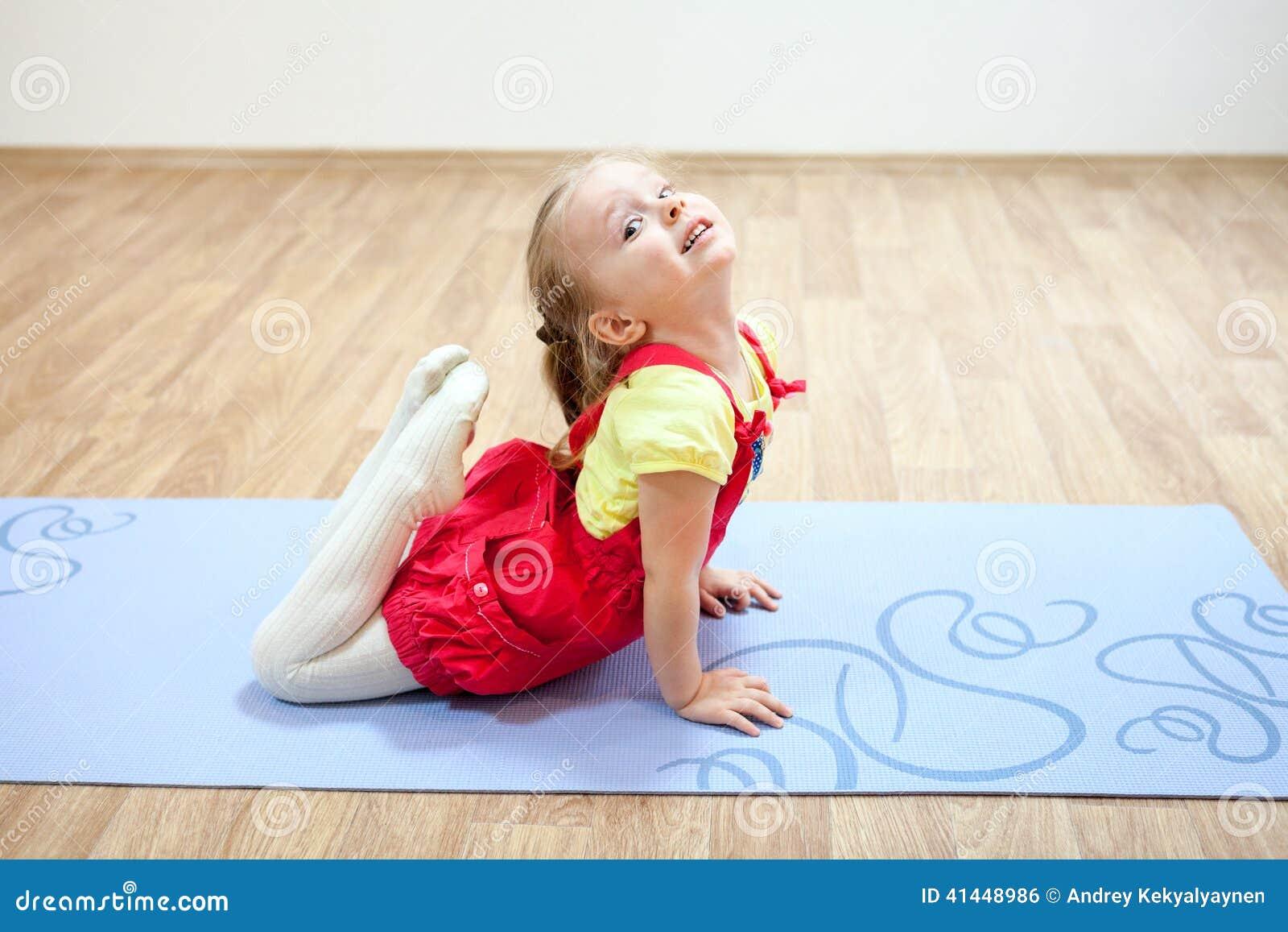 La ragazza graziosa che fa l yoga posa sulla stuoia in palestra