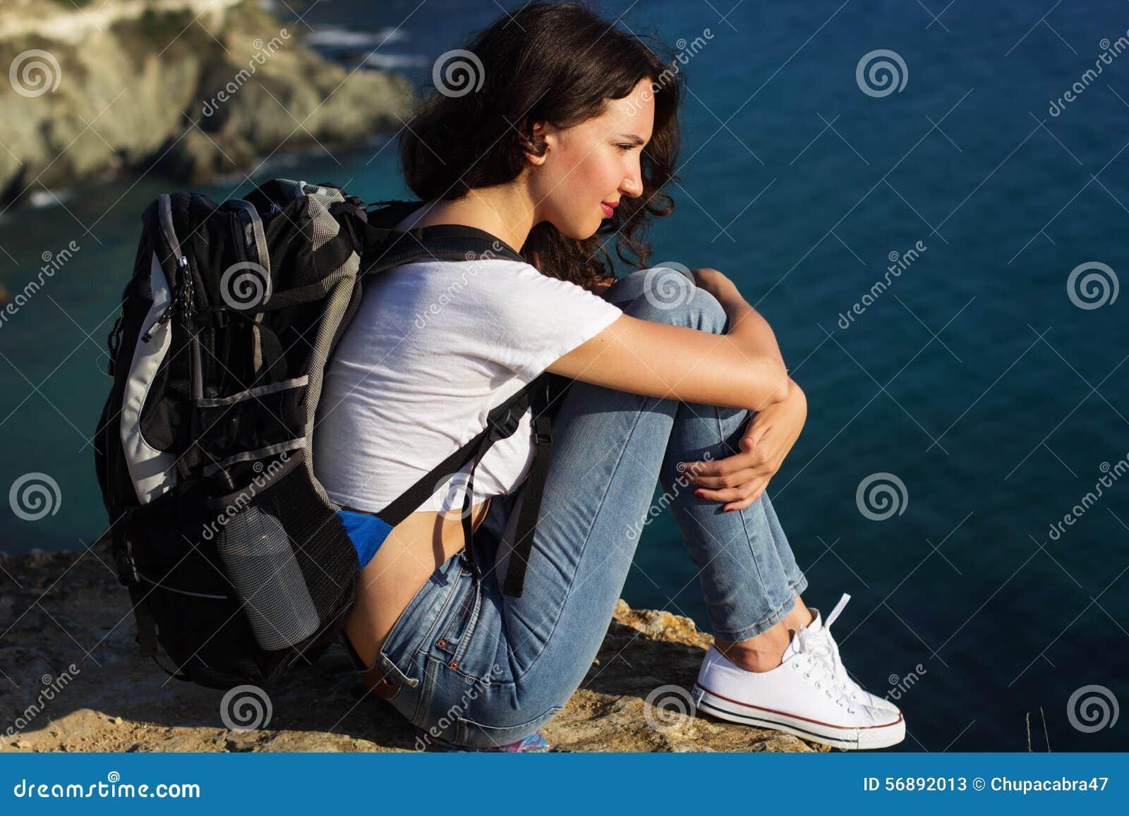 La ragazza graziosa sta sedendosi sulla roccia con lo zaino