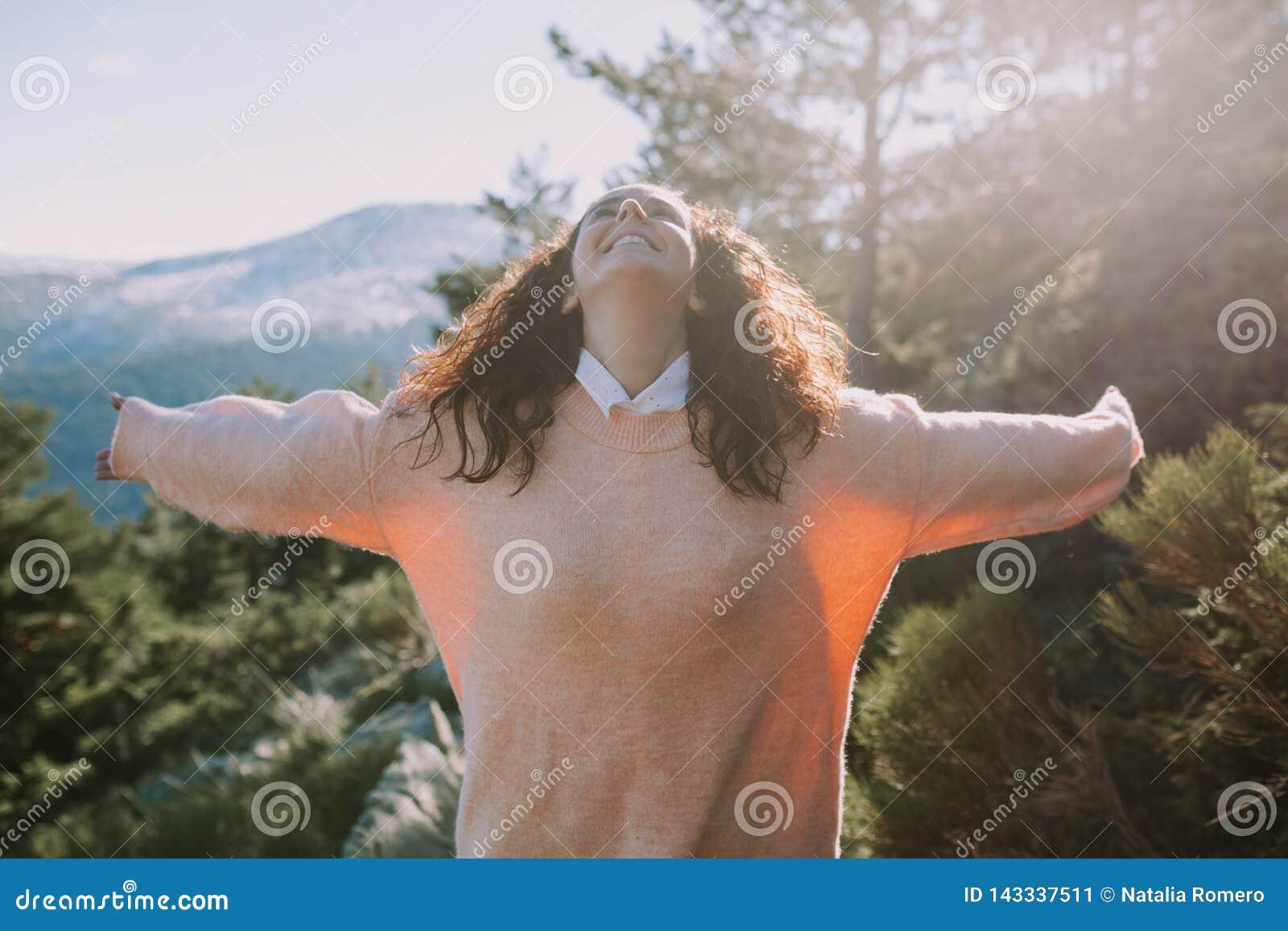 La ragazza graziosa in un maglione colorato di corallo sparge le sue armi con un fronte felice