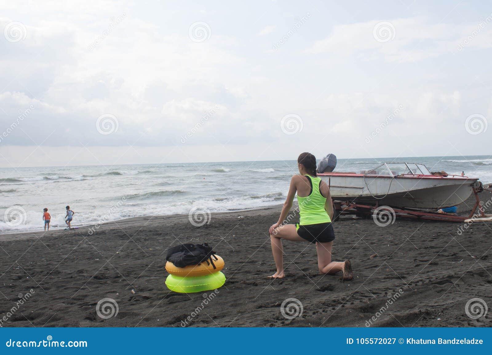 La ragazza, il fuoribordo ed il giallo, anello di galleggiamento verde sulla spiaggia, annuvolamento, nuvole, ondeggia