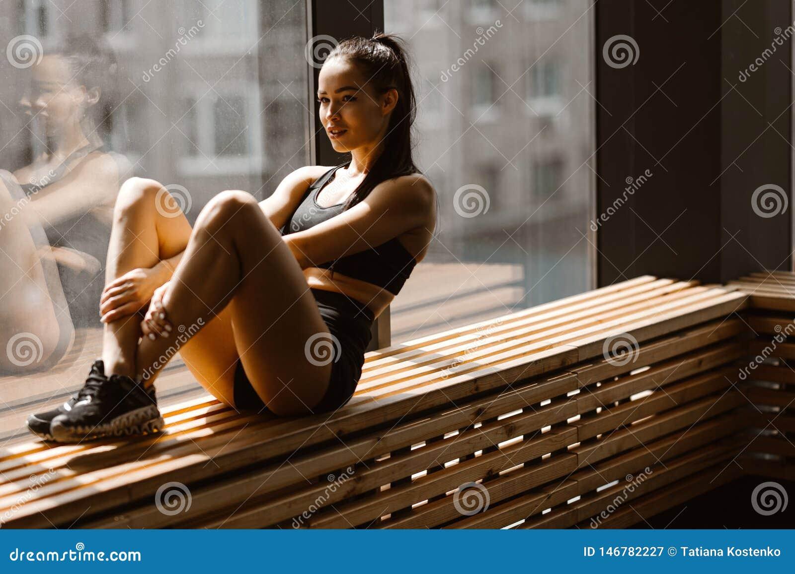 La ragazza mora atletica vestita negli sport neri superiori e mette sta sedendosi su un davanzale di legno della finestra nella p