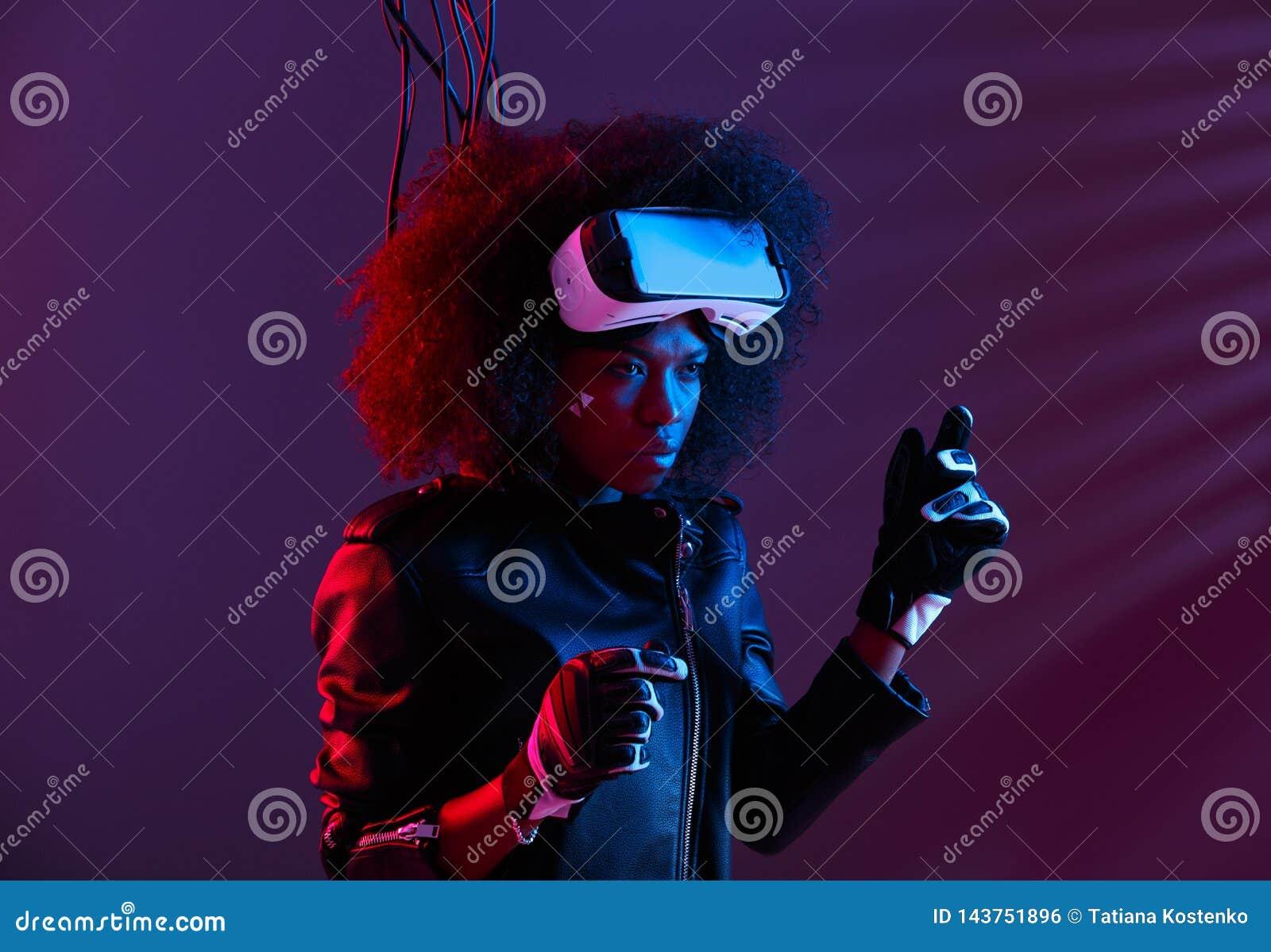 La ragazza mora riccia alla moda vestita in bomber ed in guanti neri sta indossando i vetri di realt? virtuale lei