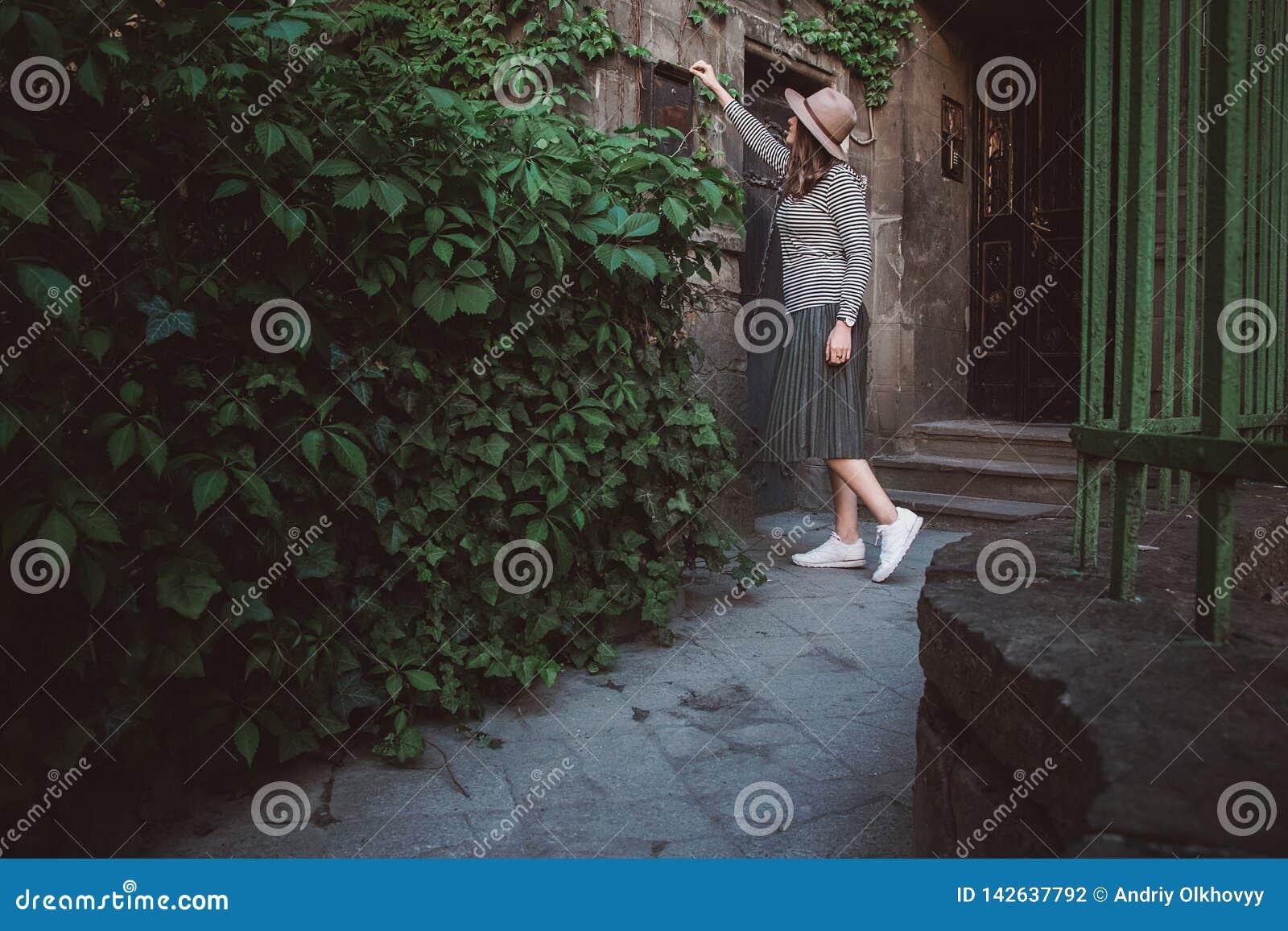 La ragazza nel cappello apre una cassetta delle lettere con gli strati ai precedenti di vecchia casa