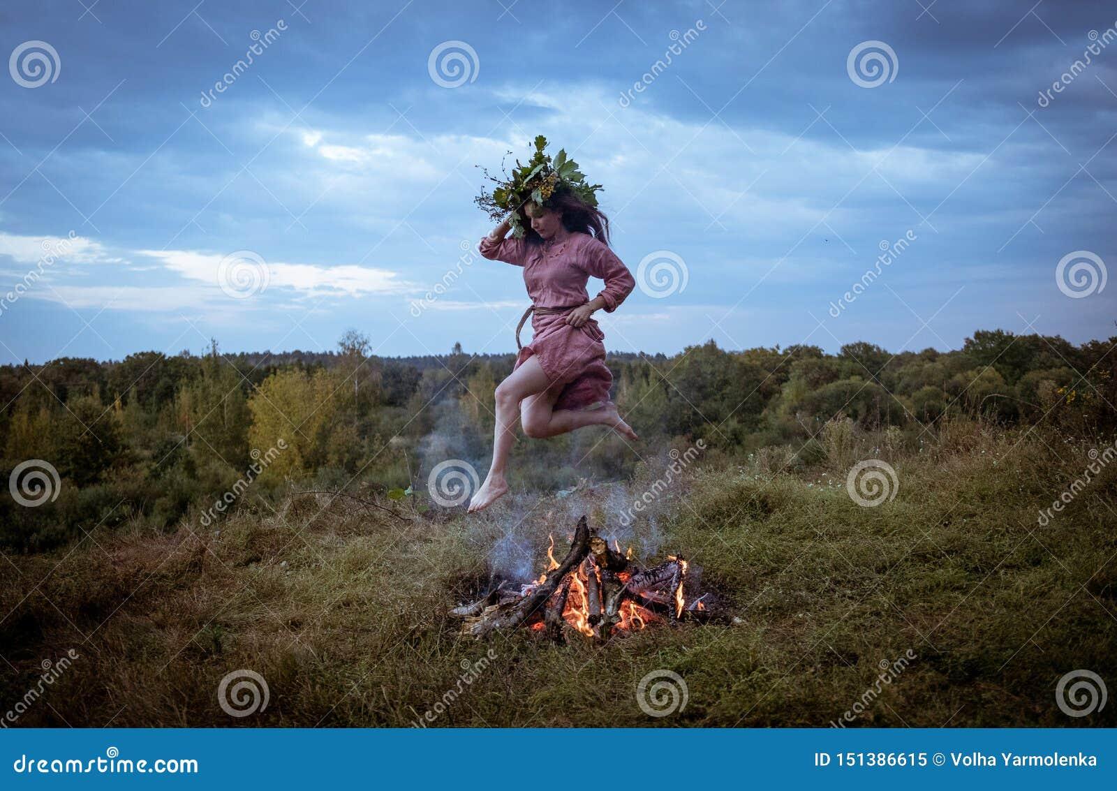 La ragazza nel costume dello slavo di Viking Age che salta sopra il fuoco