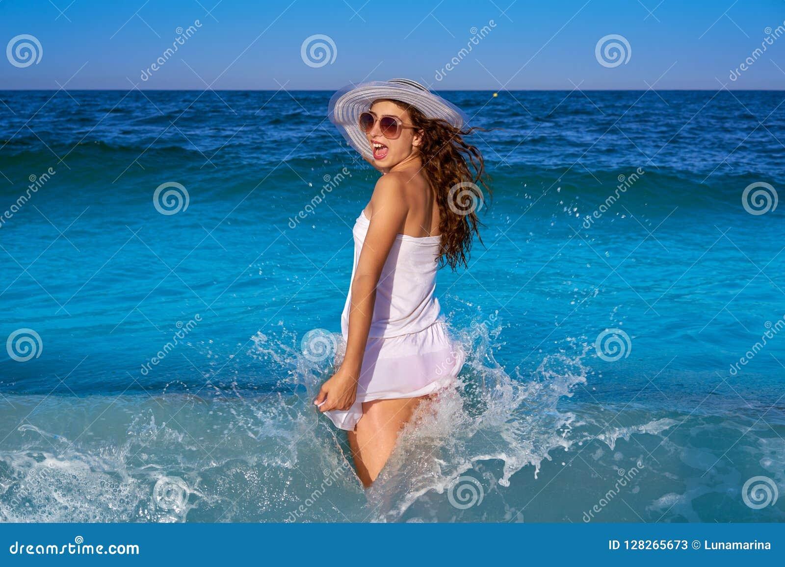 3fc266ad698f La ragazza nella riva di mare della spiaggia con le onde spruzza ed il vestito  bianco dall estate
