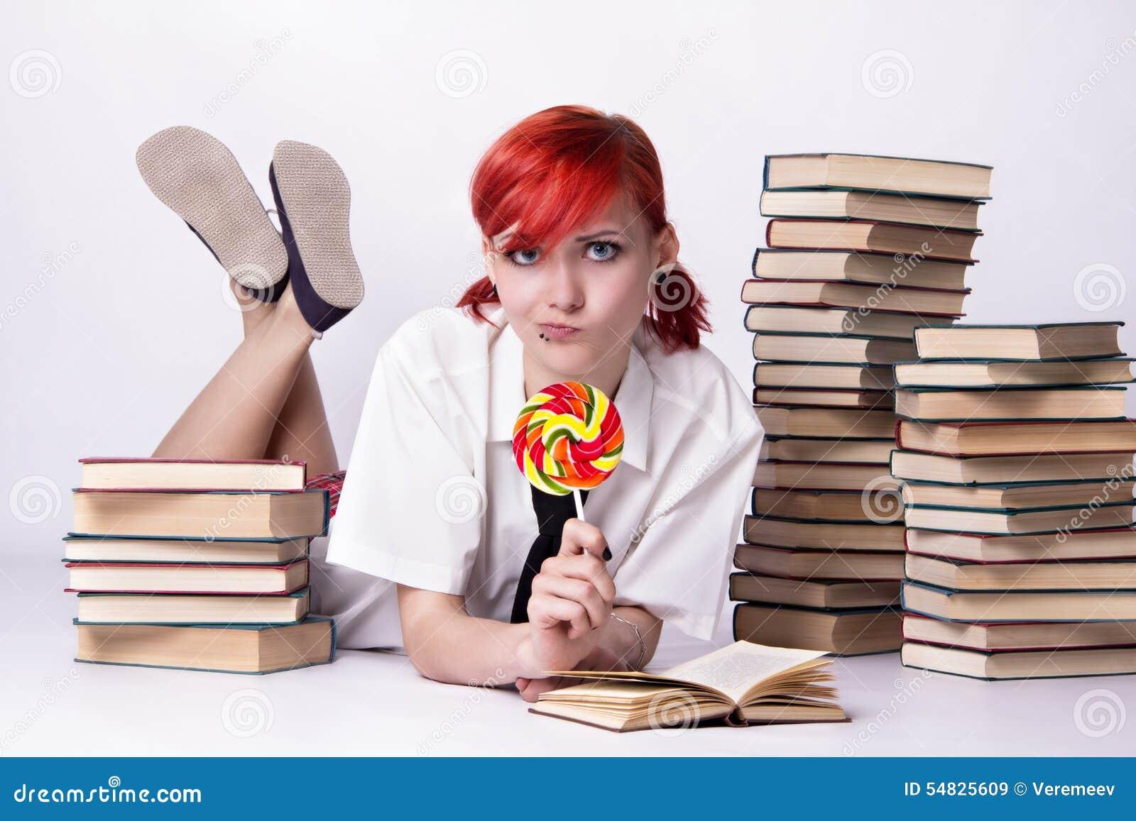 La ragazza nello stile di anime con la caramella ed i libri