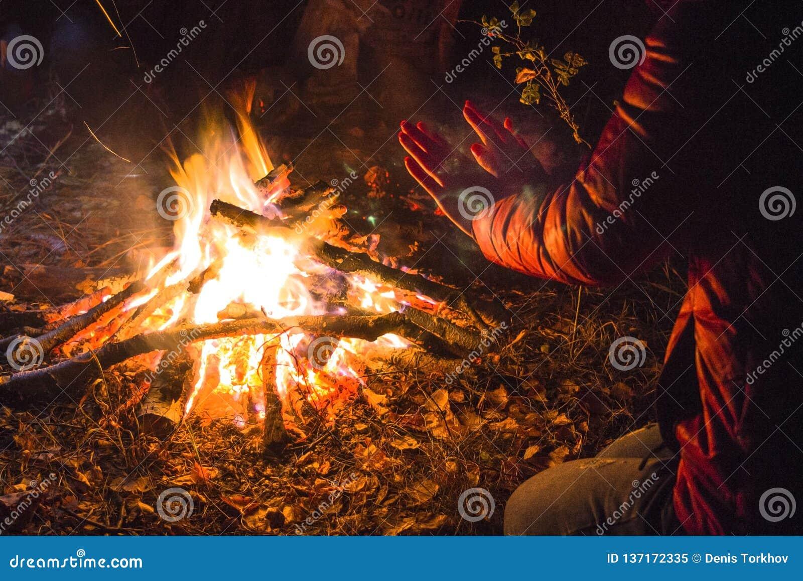 La ragazza riscalda le sue mani dal fuoco nella foresta di notte