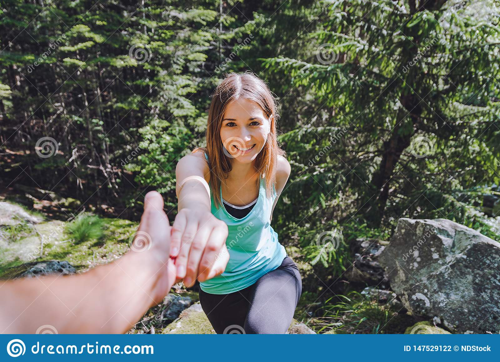 La ragazza scala su roccia, partner estrae la mano per assistenza