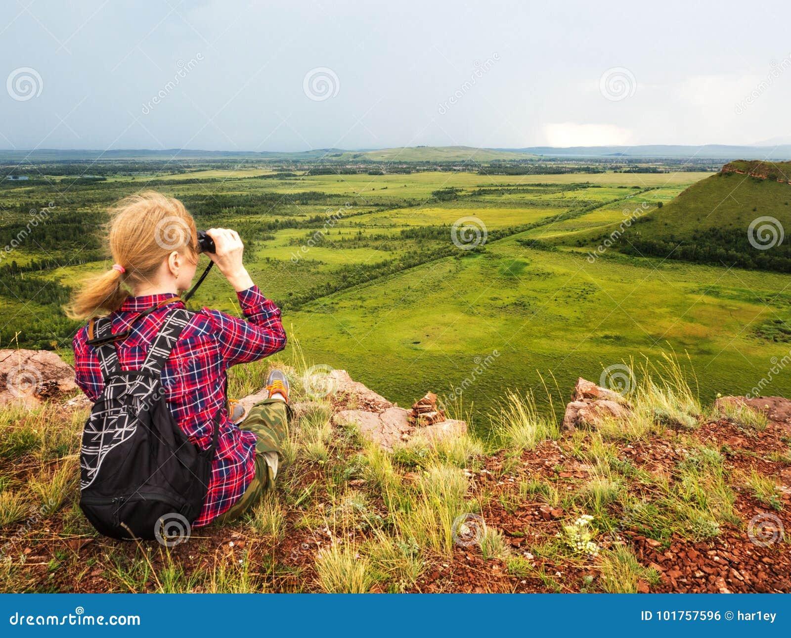 La ragazza si siede sulla montagna e esamina la distanza con il binocolo