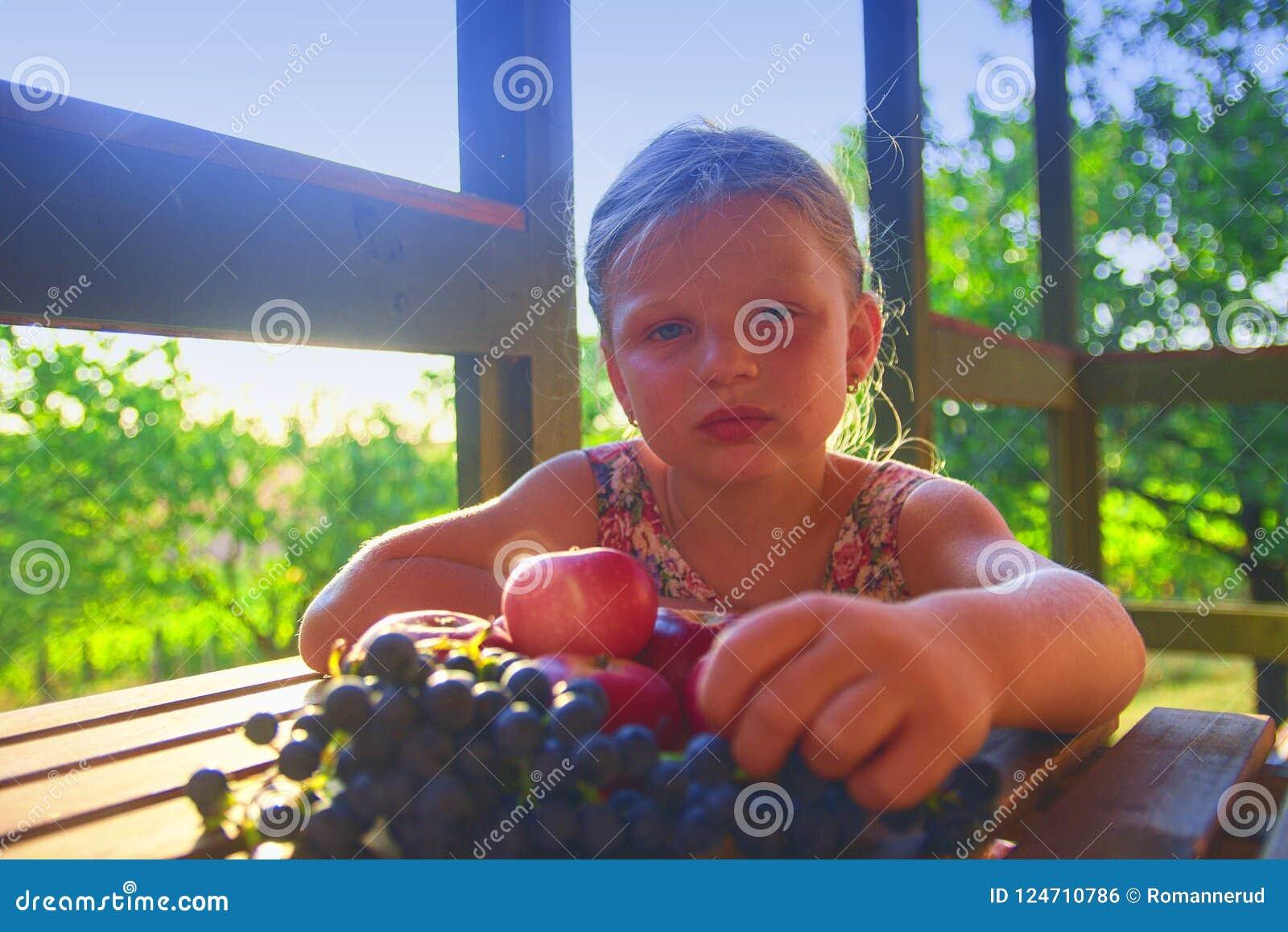 La ragazza sta mangiando la frutta Mele ed uva su una tavola La bambina sta sedendosi ad una tavola su una veranda e su un eati