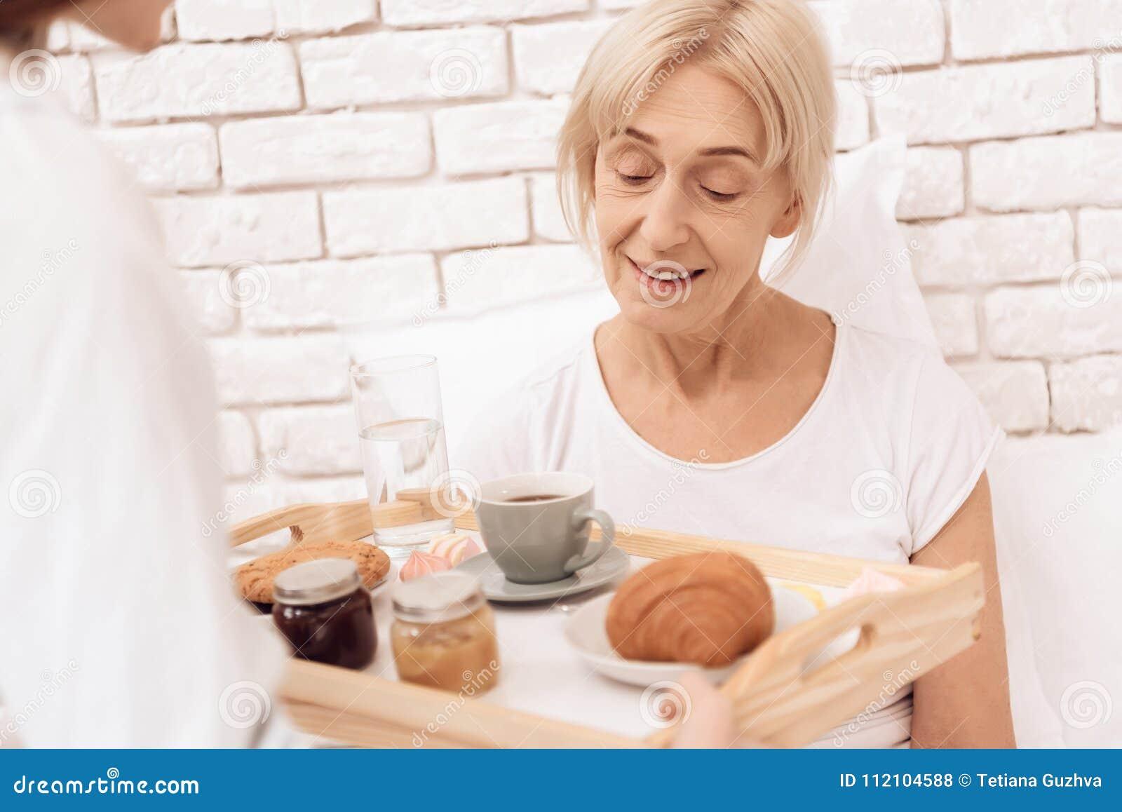 La ragazza sta occupandosi della donna anziana a casa La ragazza porta la prima colazione sul vassoio