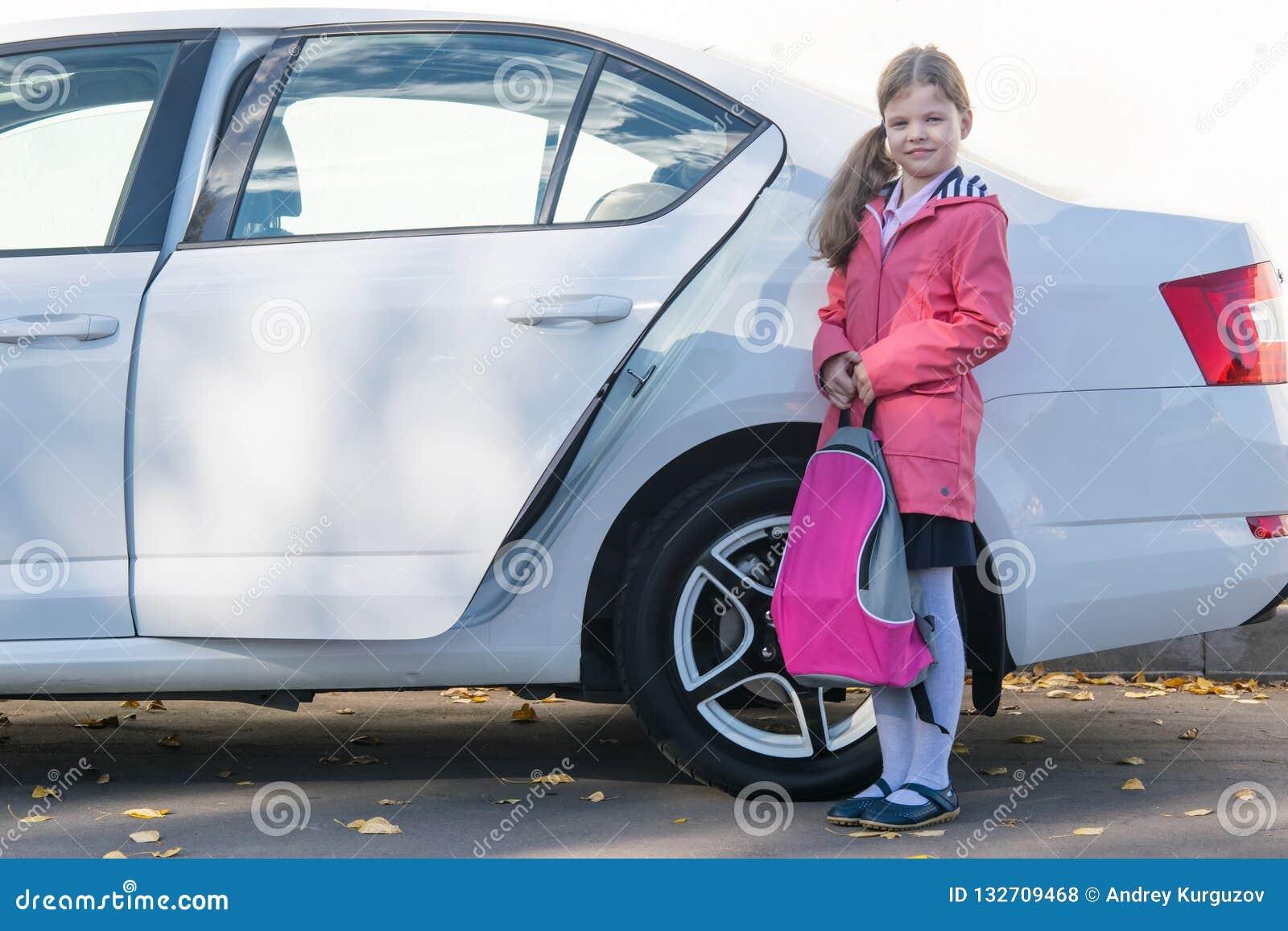 La ragazza stava andando in viaggio in macchina ad una istituzione-scuola educativa, con una cartella in sue mani