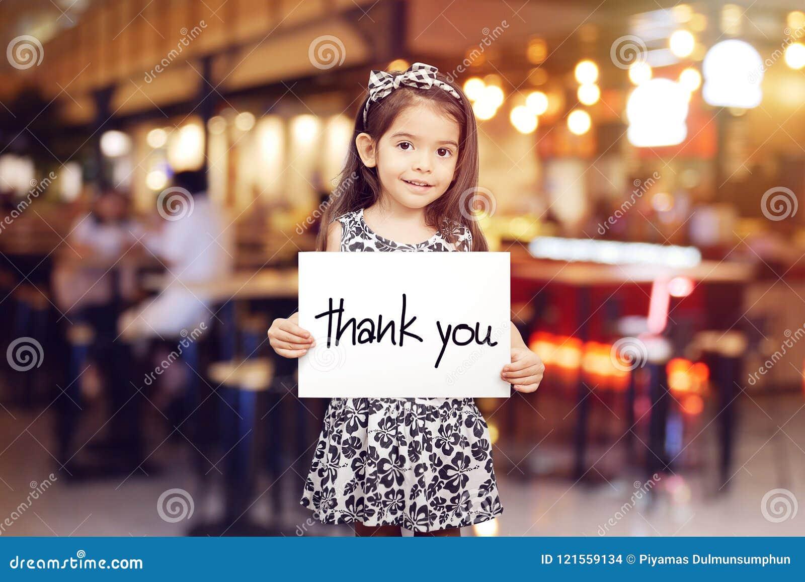 La ragazza sveglia che tiene pezzo di carta con le parole vi ringrazia