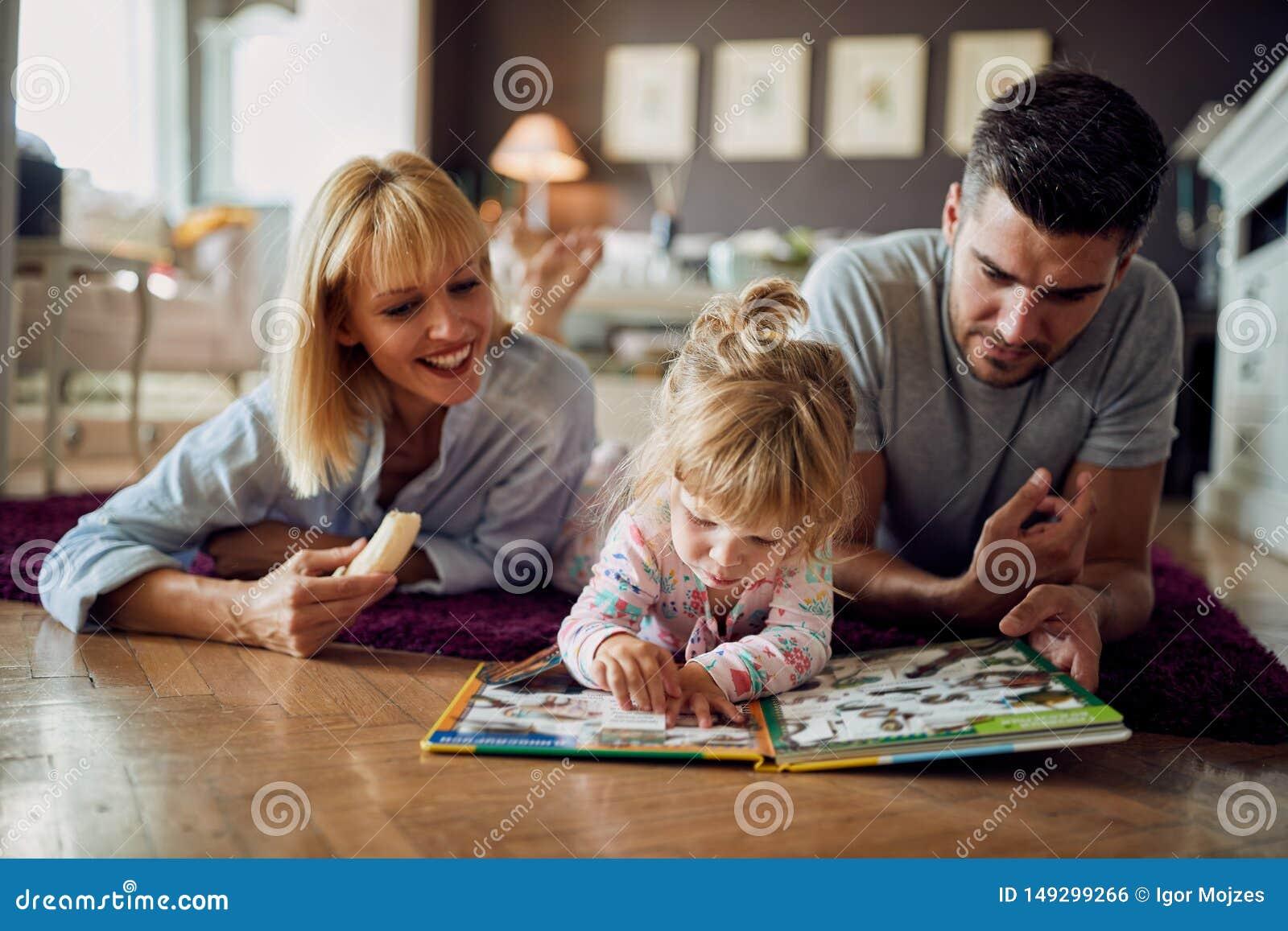 La ragazza sveglia con i genitori gioca con il puzzle dell interno