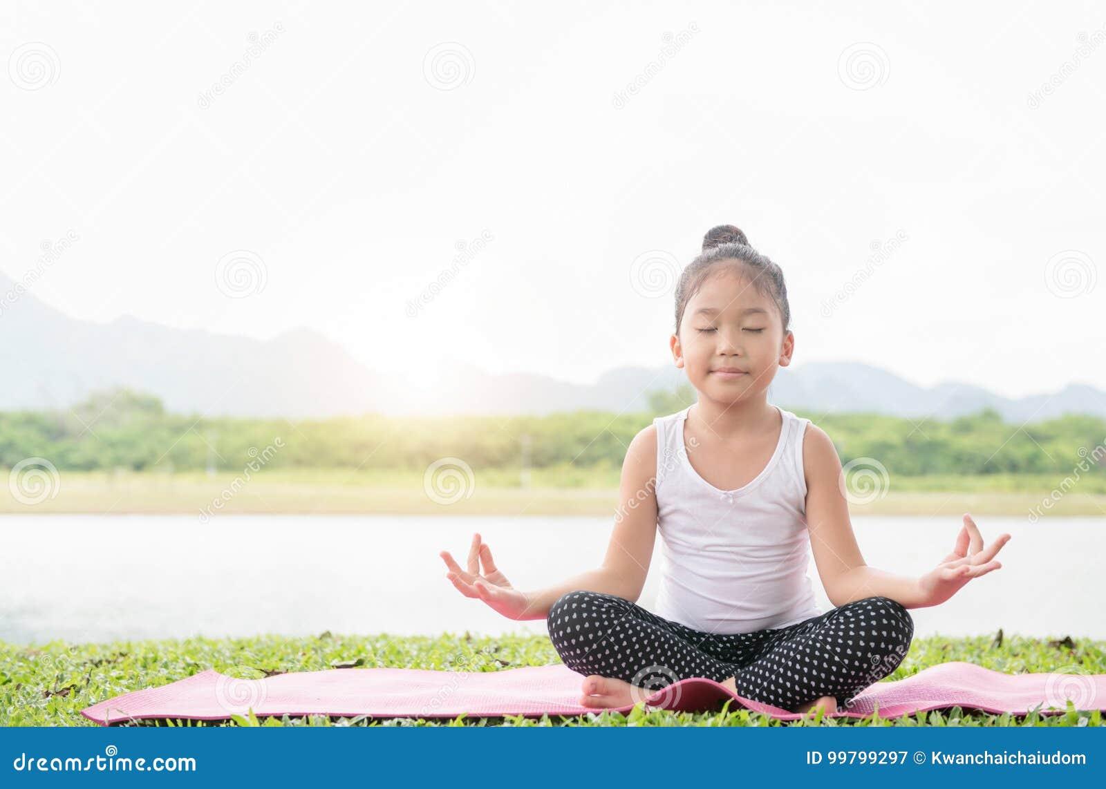La ragazza sveglia felice pratica l yoga e medita nel positi del loto