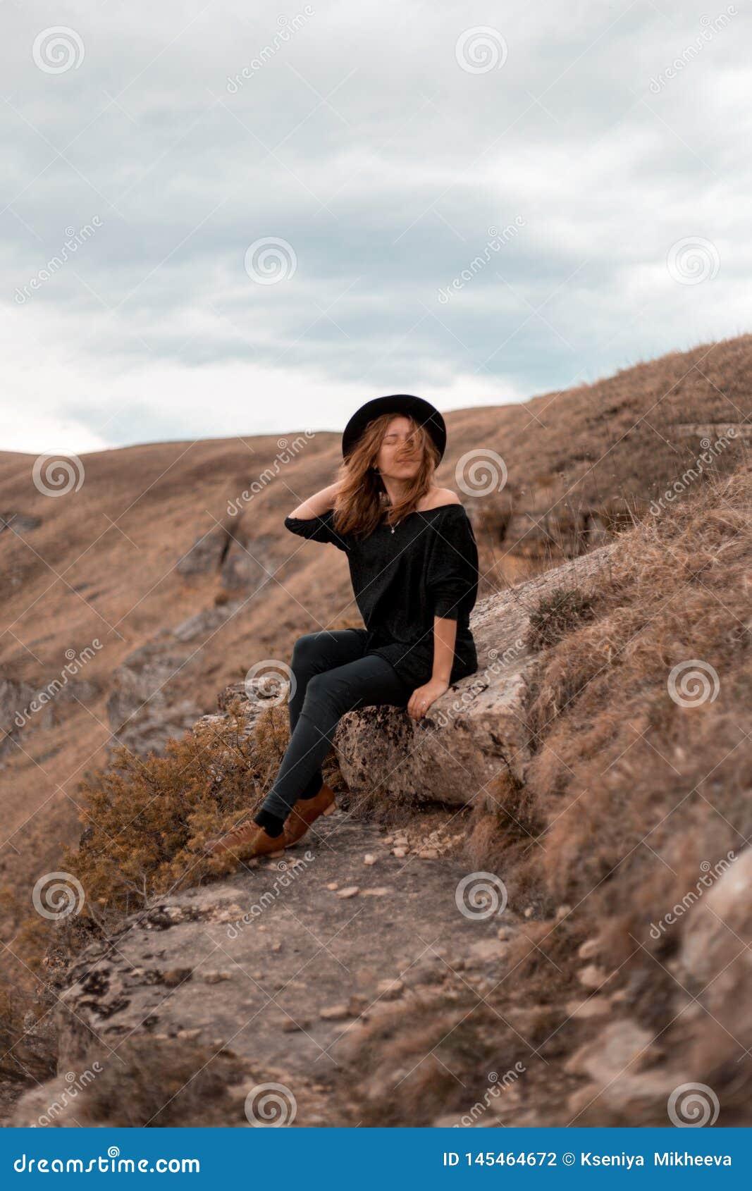 La ragazza tiene il suo cappello, girante la di nuovo alla valle con le montagne sieda su roccia