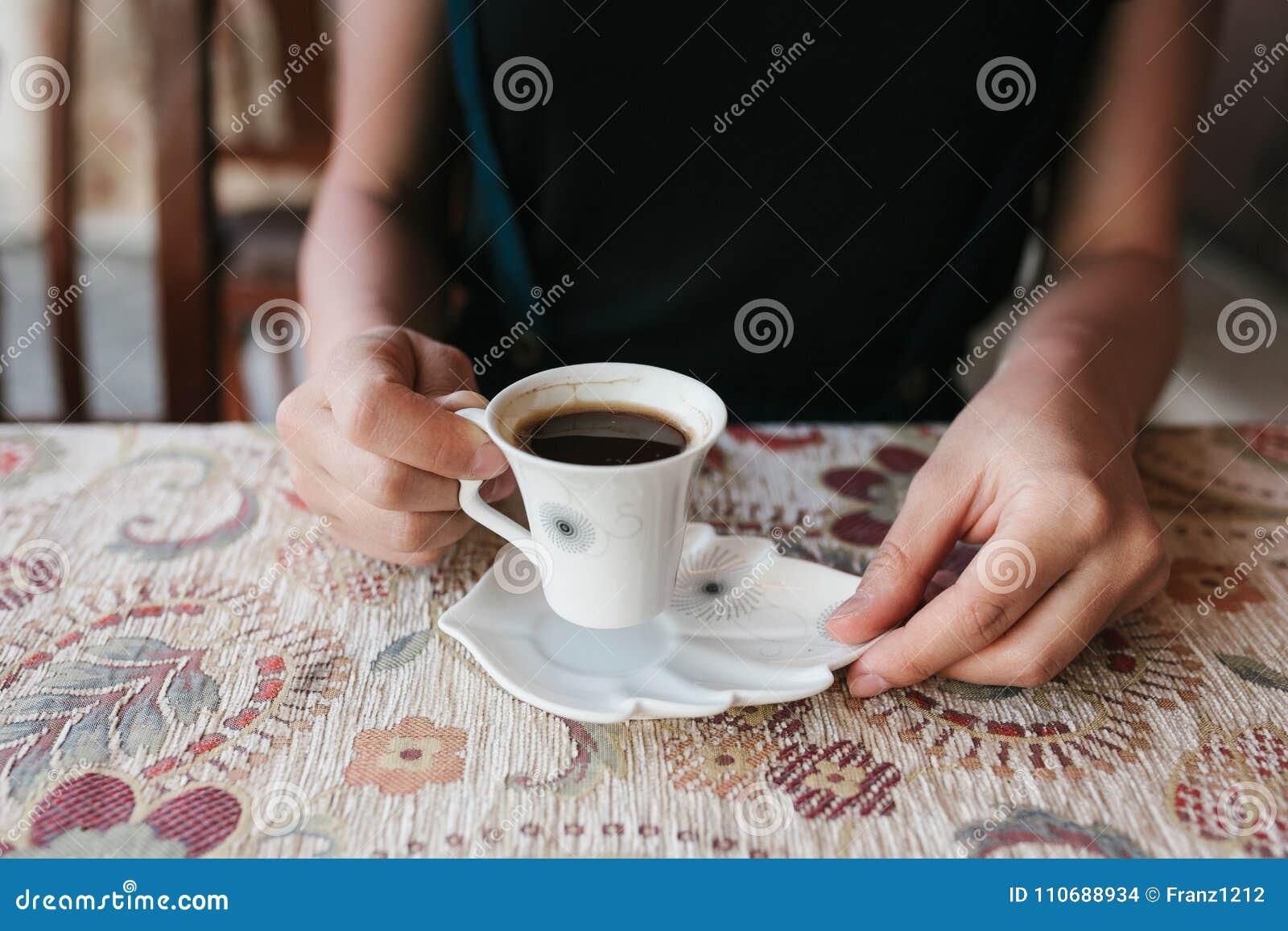 La ragazza tiene una tazza di caffè turco tradizionale aromatico naturale in un caffè della via