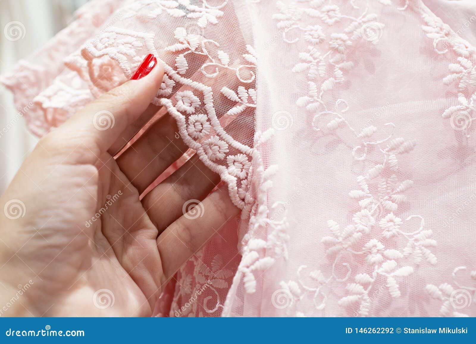 La ragazza tocca il pizzo rosa delicato