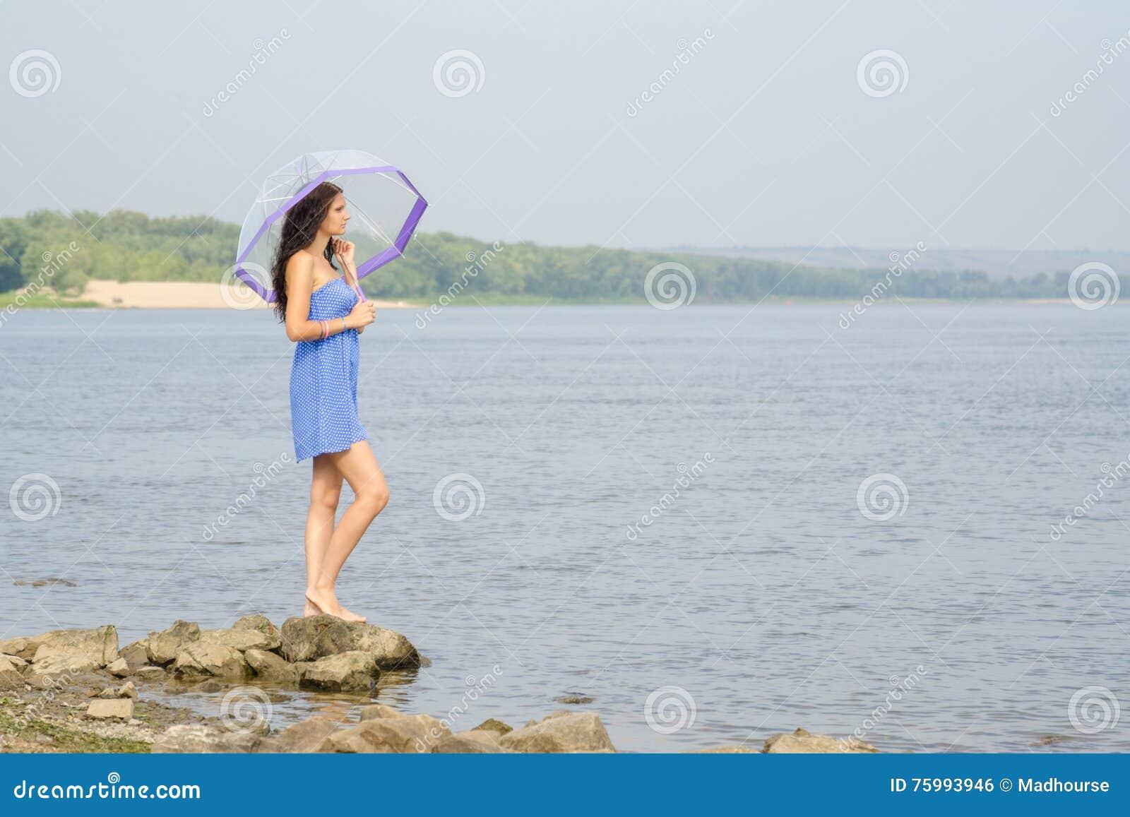 La ragazza triste sola con portaombrelli sulla banca del fiume e esamina la distanza