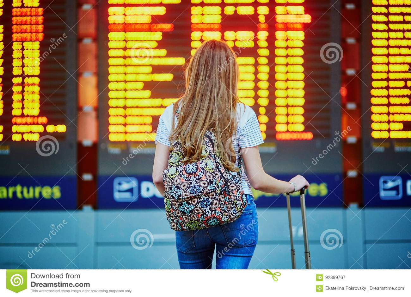 La ragazza turistica con lo zaino e continua i bagagli in aeroporto internazionale, vicino al bordo di informazioni di volo