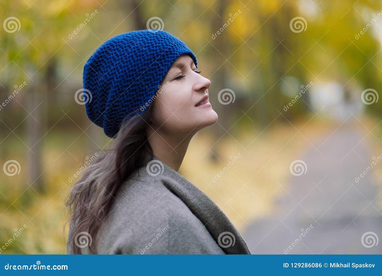 La ragazza in un cappotto ed in un cappello blu su un fondo degli alberi e delle foglie di acero di autunno